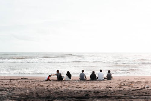 Group of People Sitting on Seashore