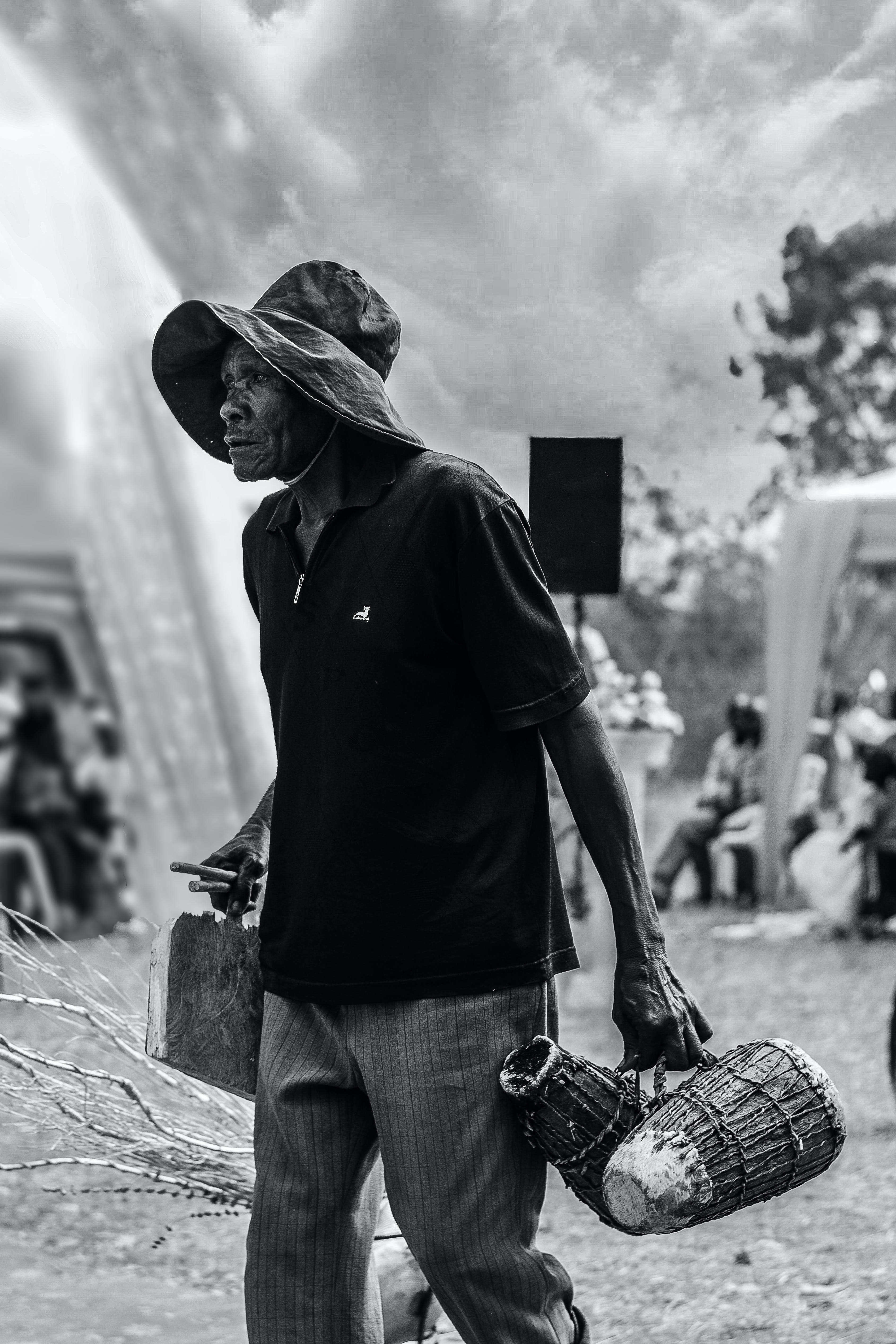 Grayscale Photography of Man Wearing Sun Hat Carrying Baskets