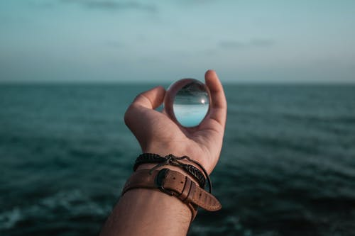 Person Holding Glass Marble Infront of Sea