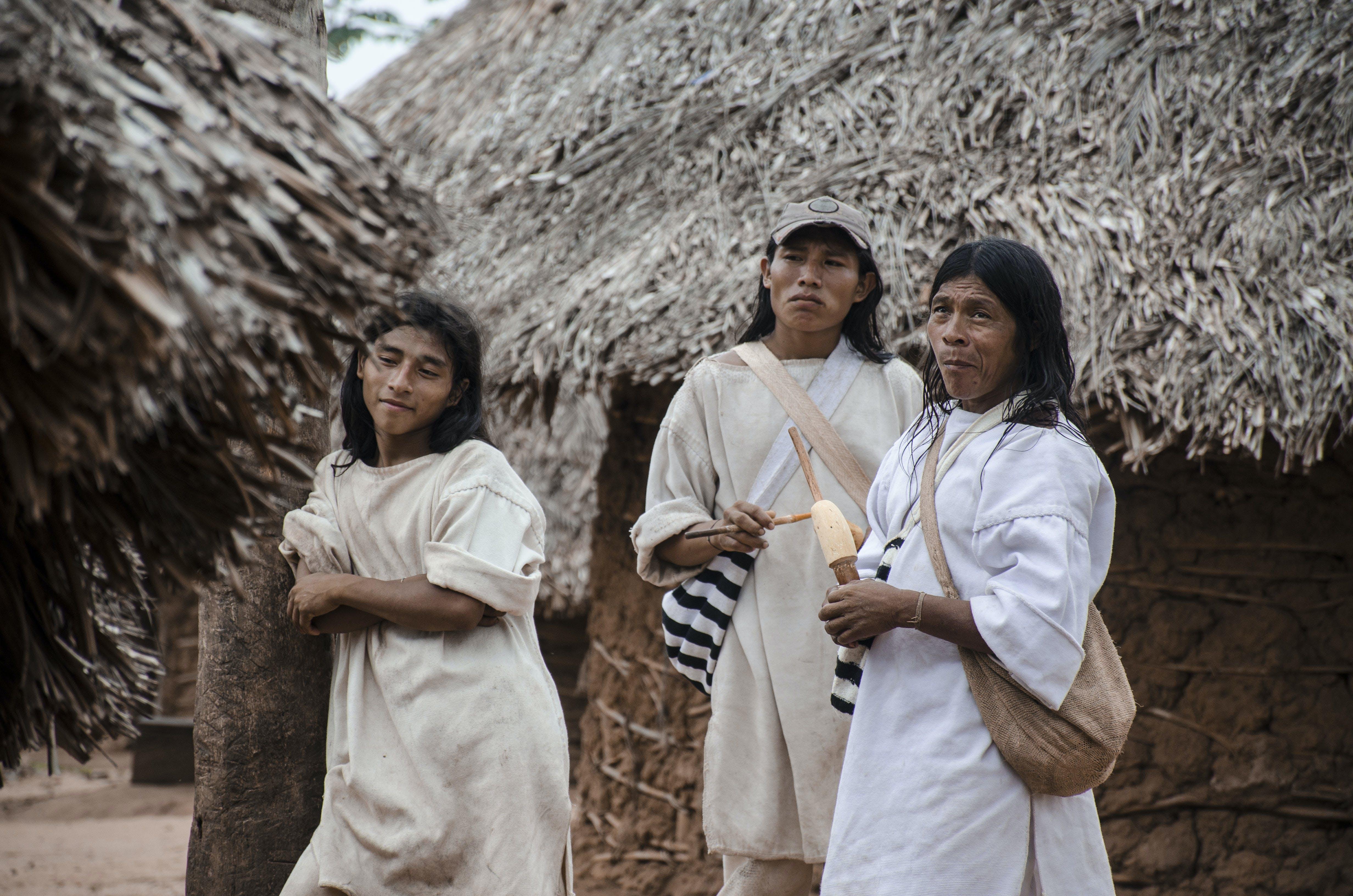 Three Man Standing Near Hut