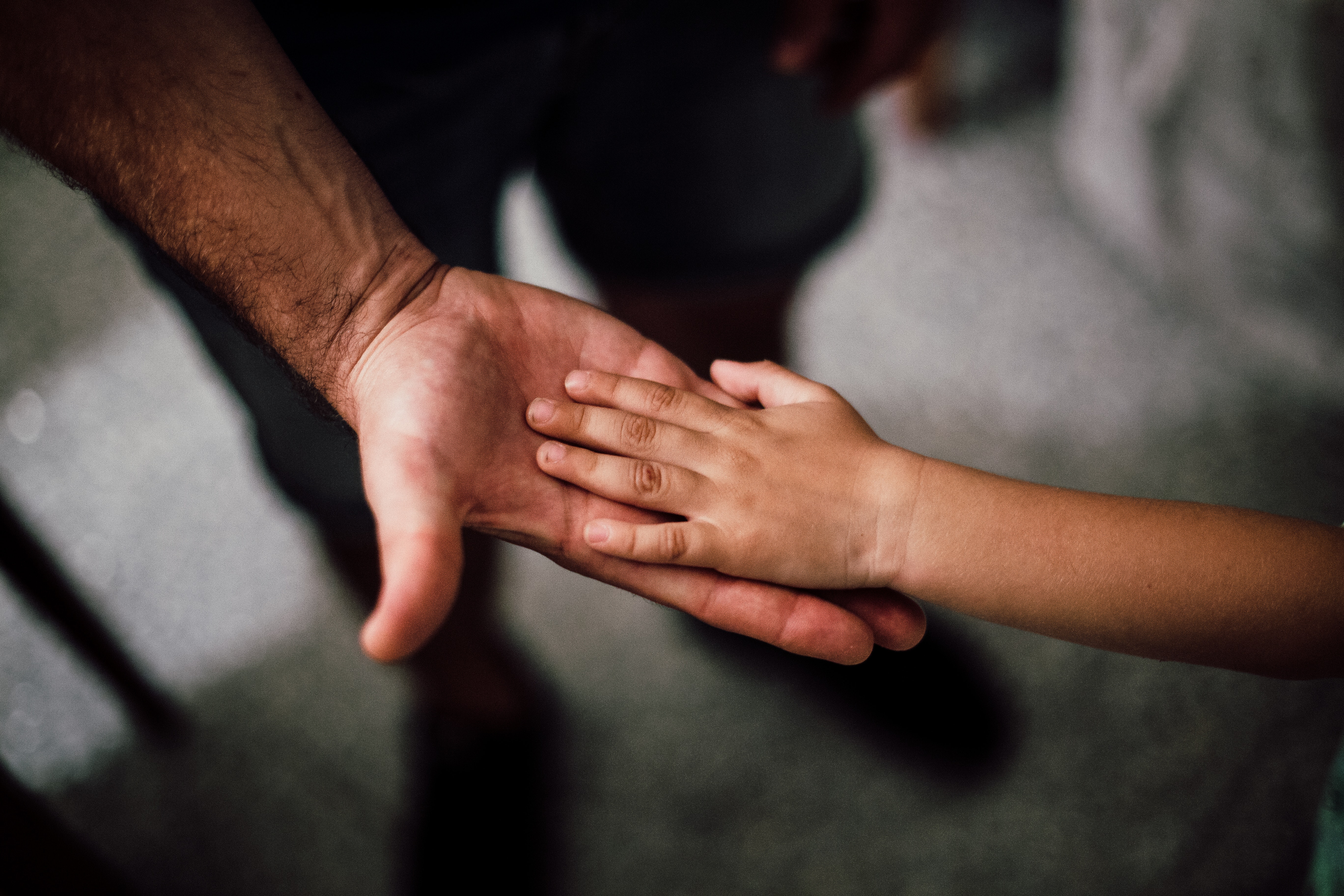 Selective focus photography of a man and a child's hand. | Photo: Pexels