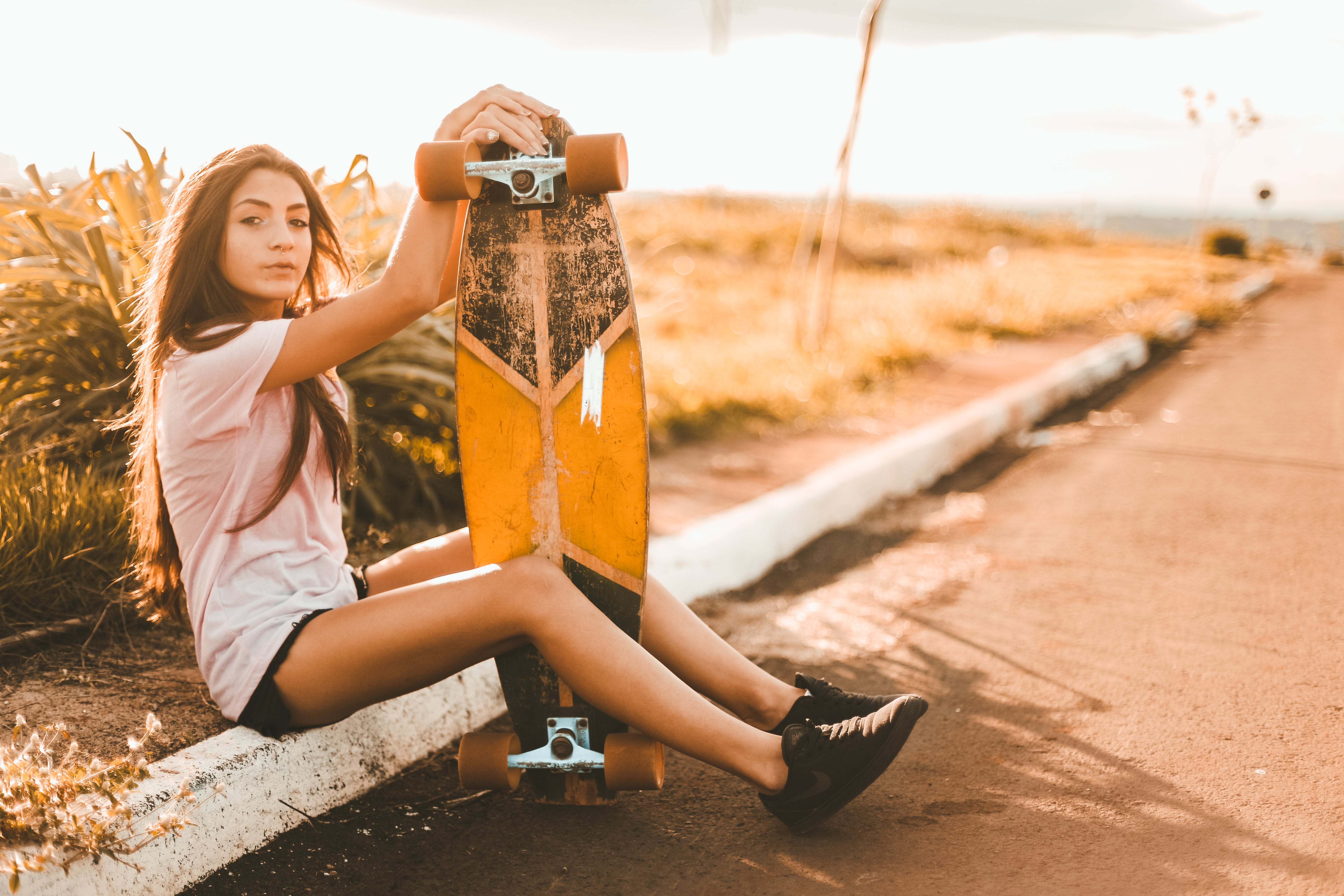 Shallow Focus Photography of Woman Holding Longboard