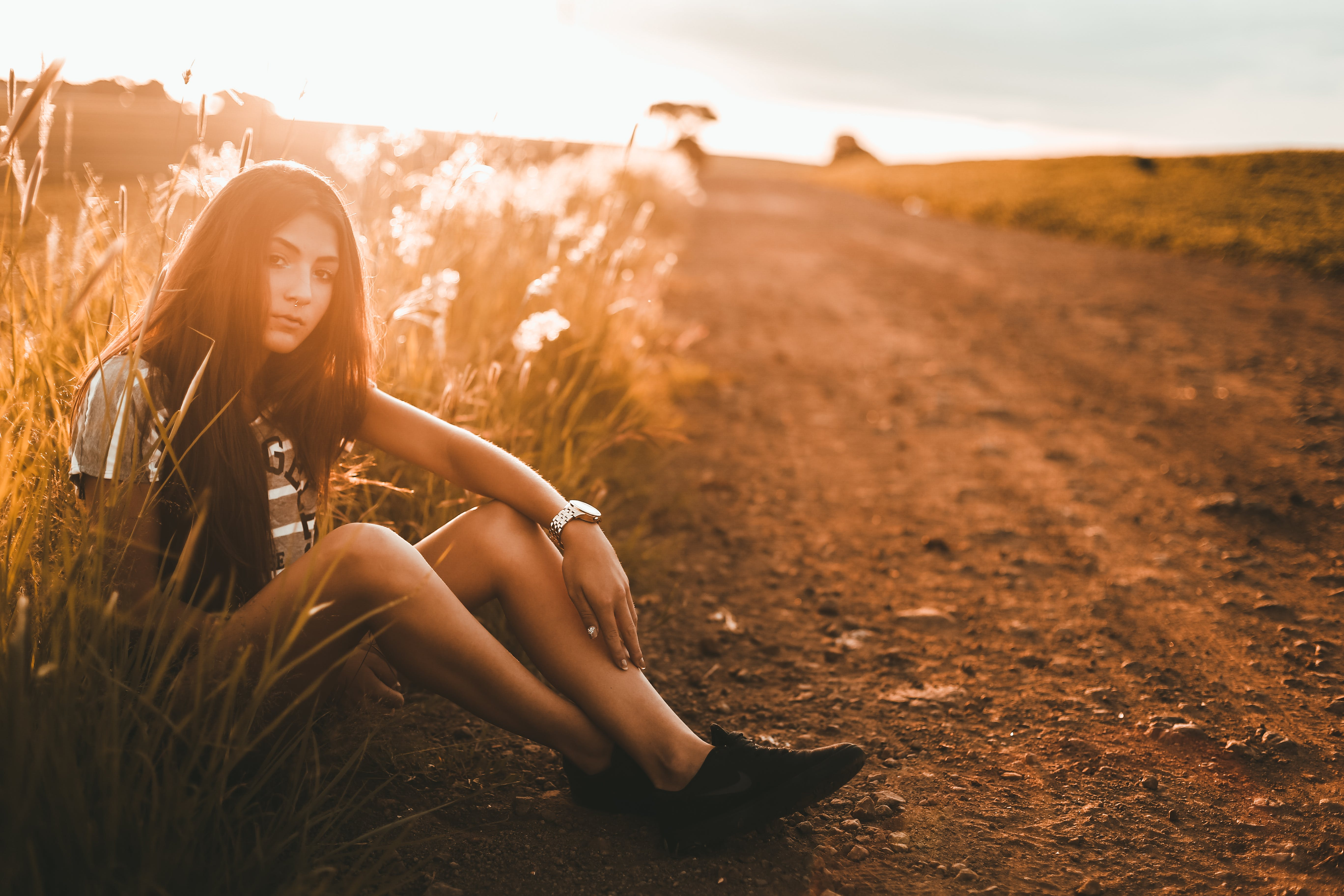 Woman Sitting on Sand Surrouded by Kans Grass during Sunset