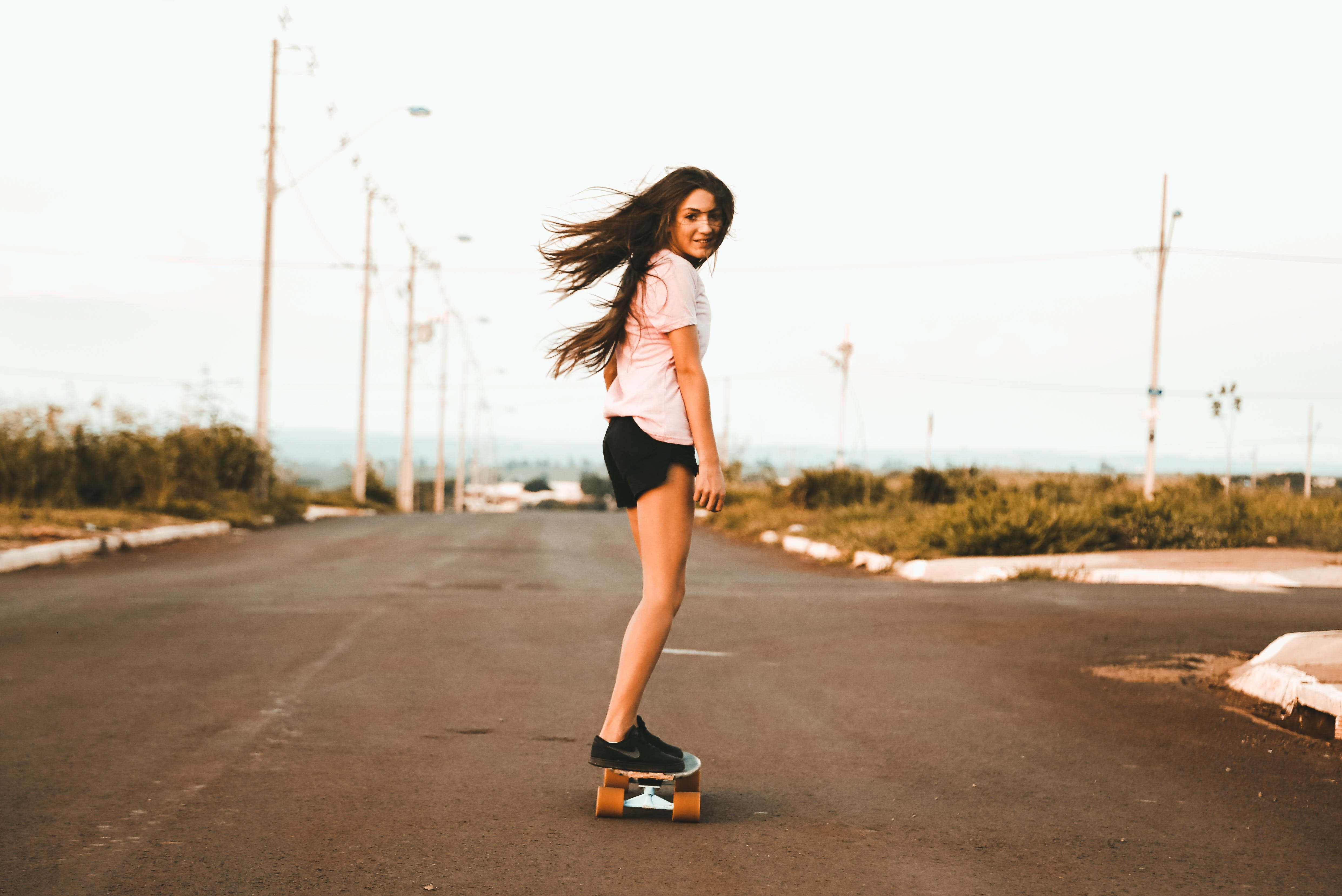 Woman Riding Skateboard at the Road