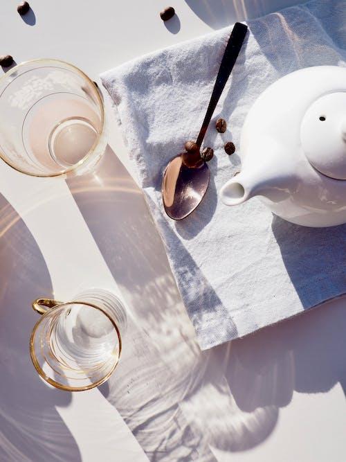 Whit Ceramic Teapot on Towel Near Spoon