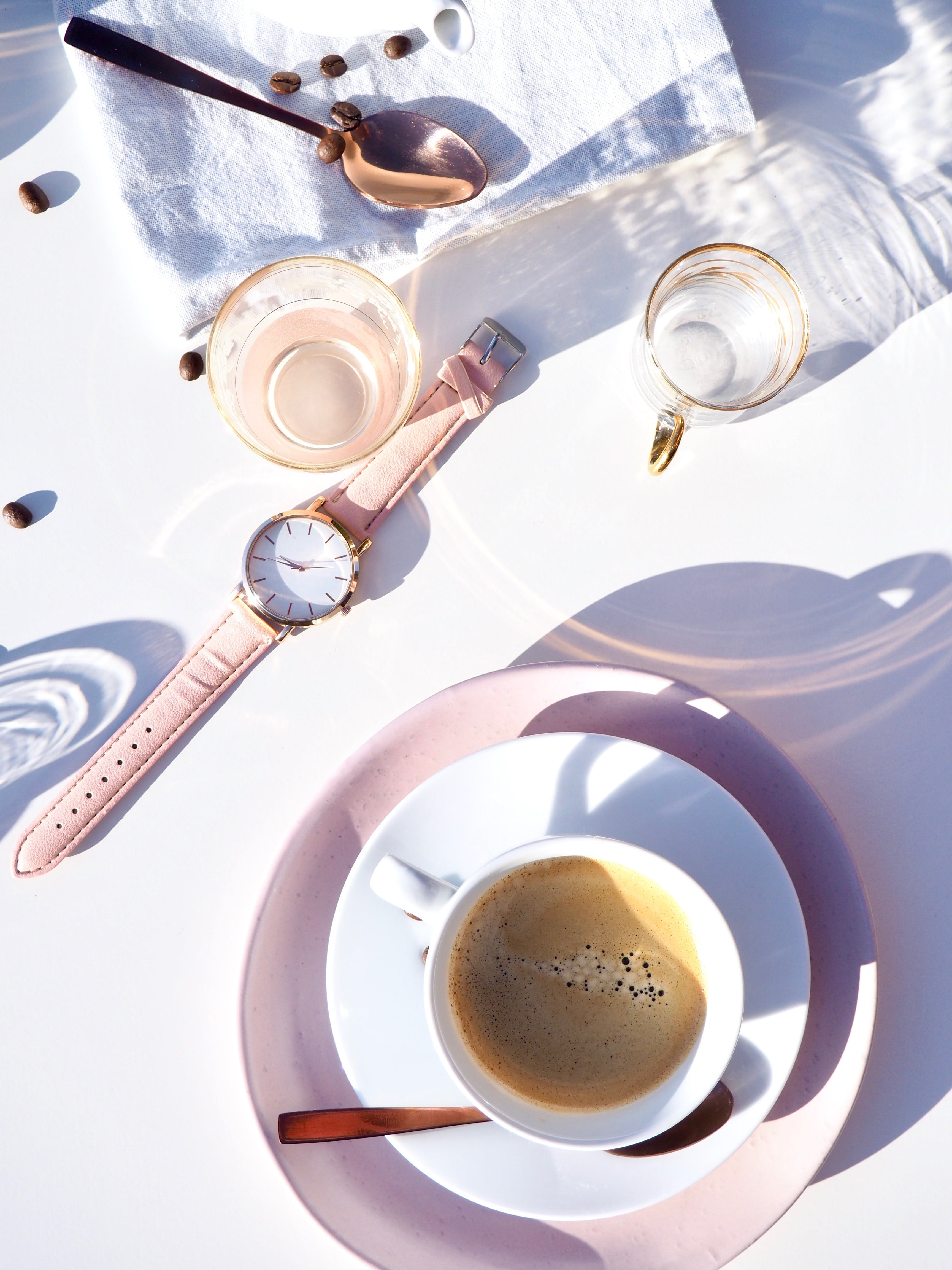 White Ceramic Cup on Saucer Near Gold-colored Analog Watch on Table