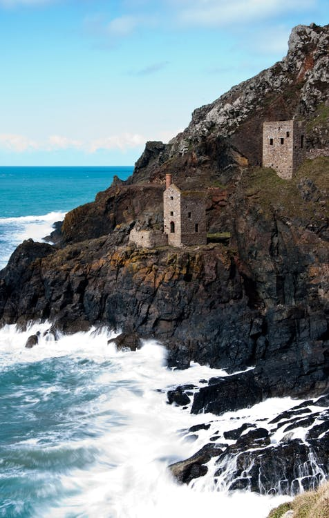 Two Gray Brick Watchtower on Cliff Near Sea at Daytime