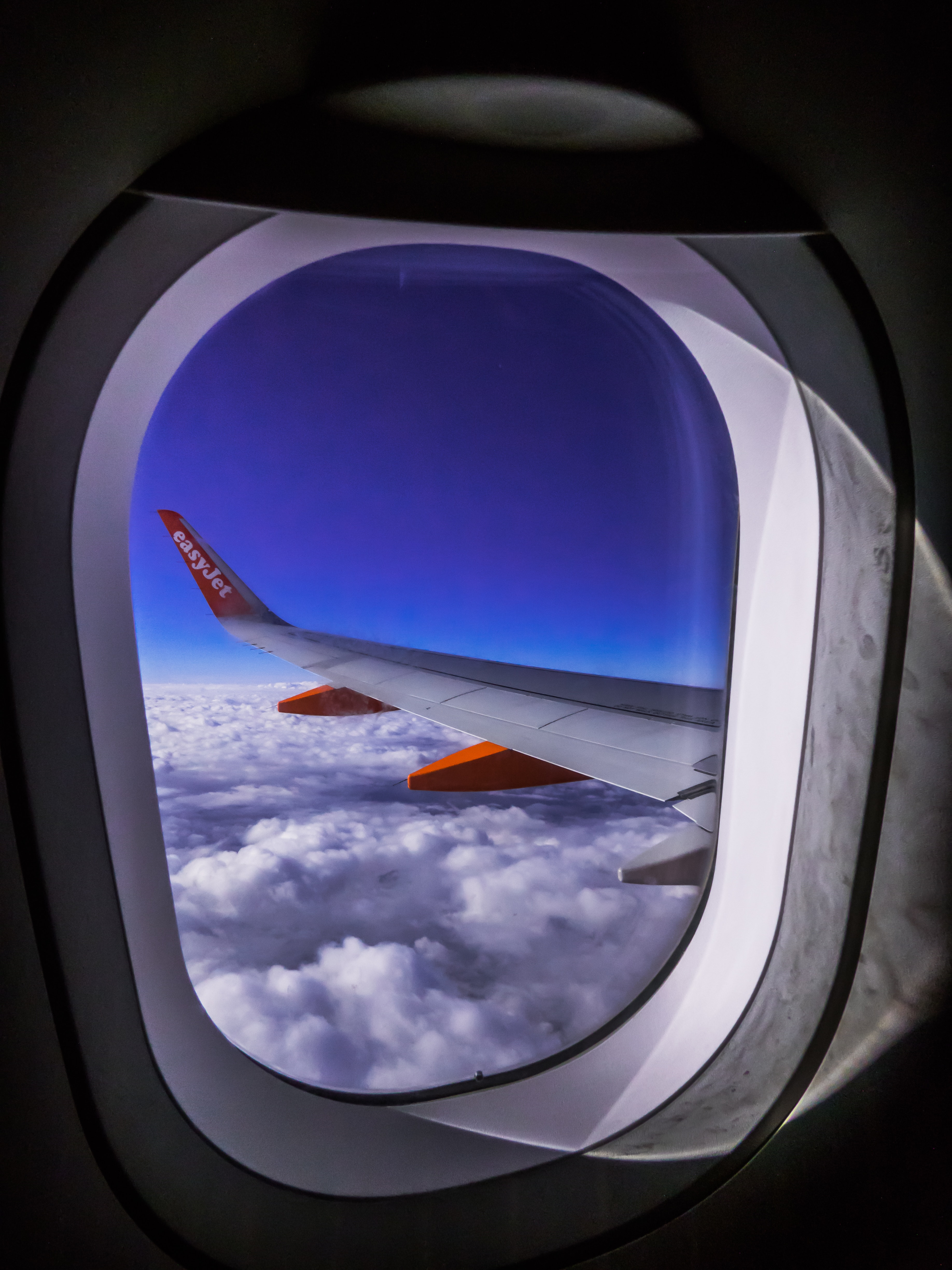 Airplane Window Overlooking Clouds Free Stock Photo