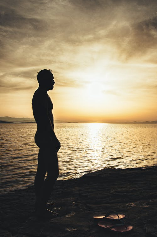 Topless Man on Sand Near Body of Water during Sunset