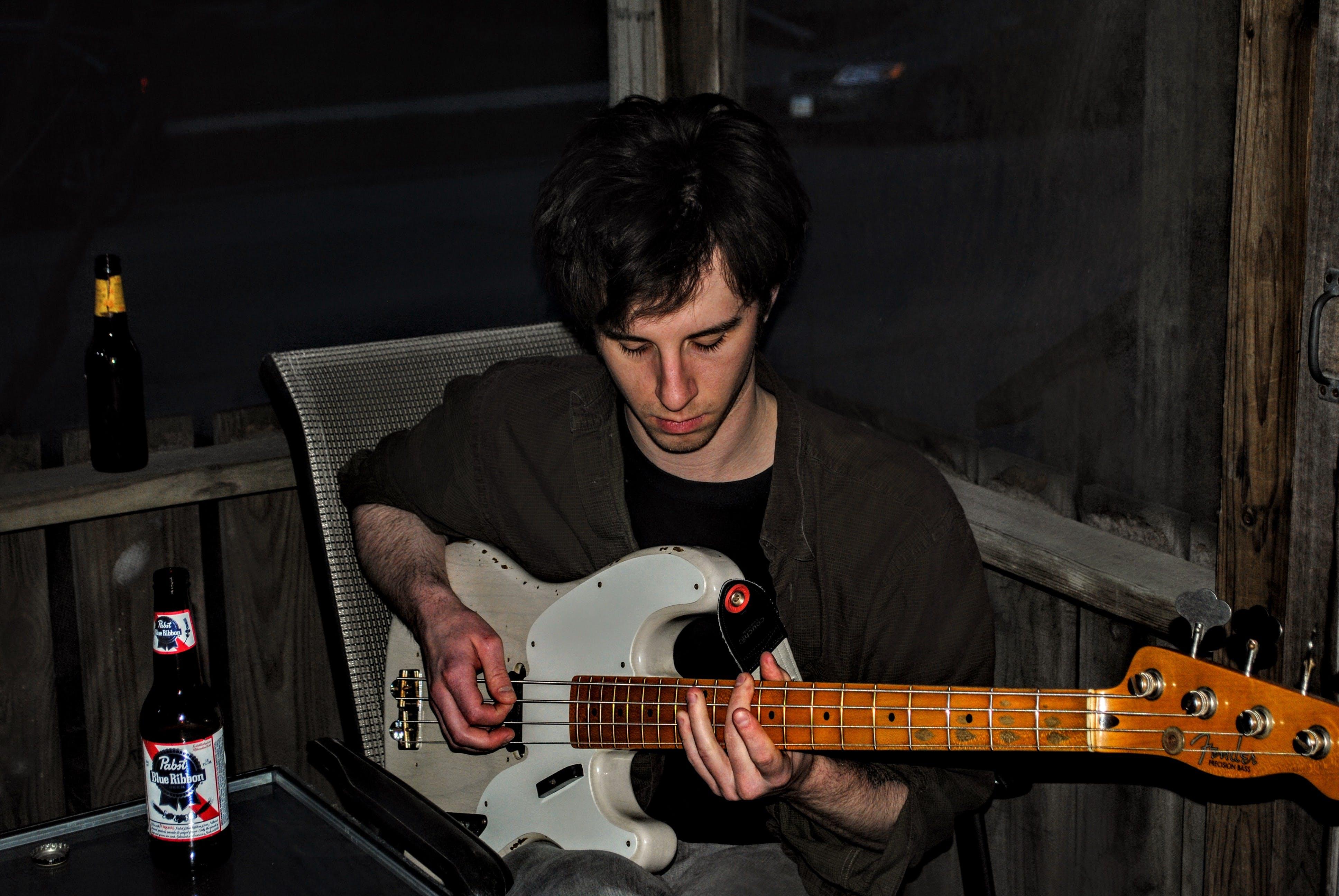 Man Playing White Electric Guitar