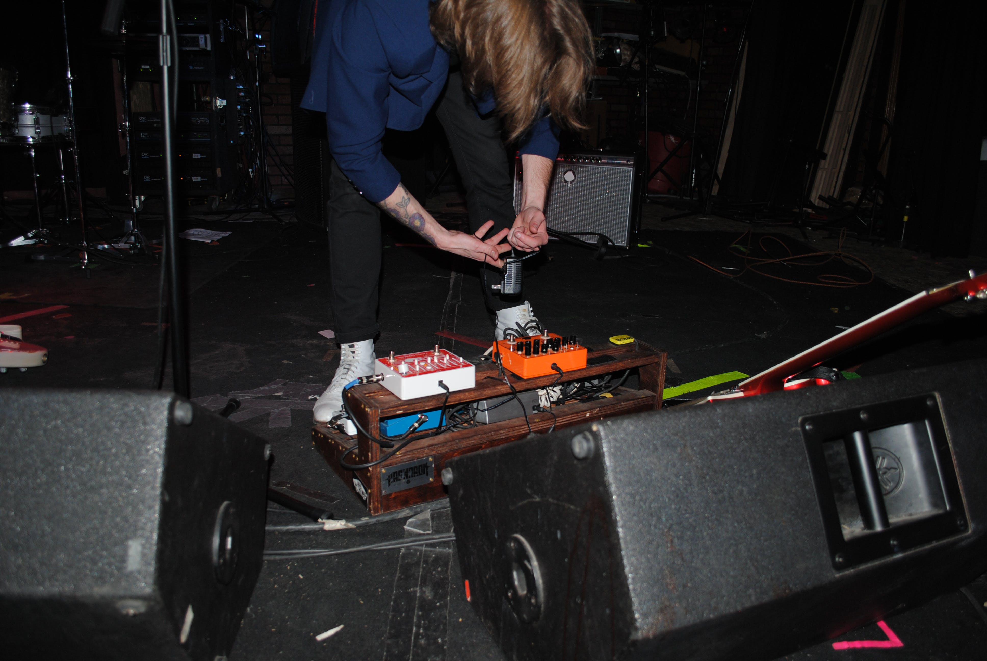 Person Standing Near Stage Speakers and Effect Pedal