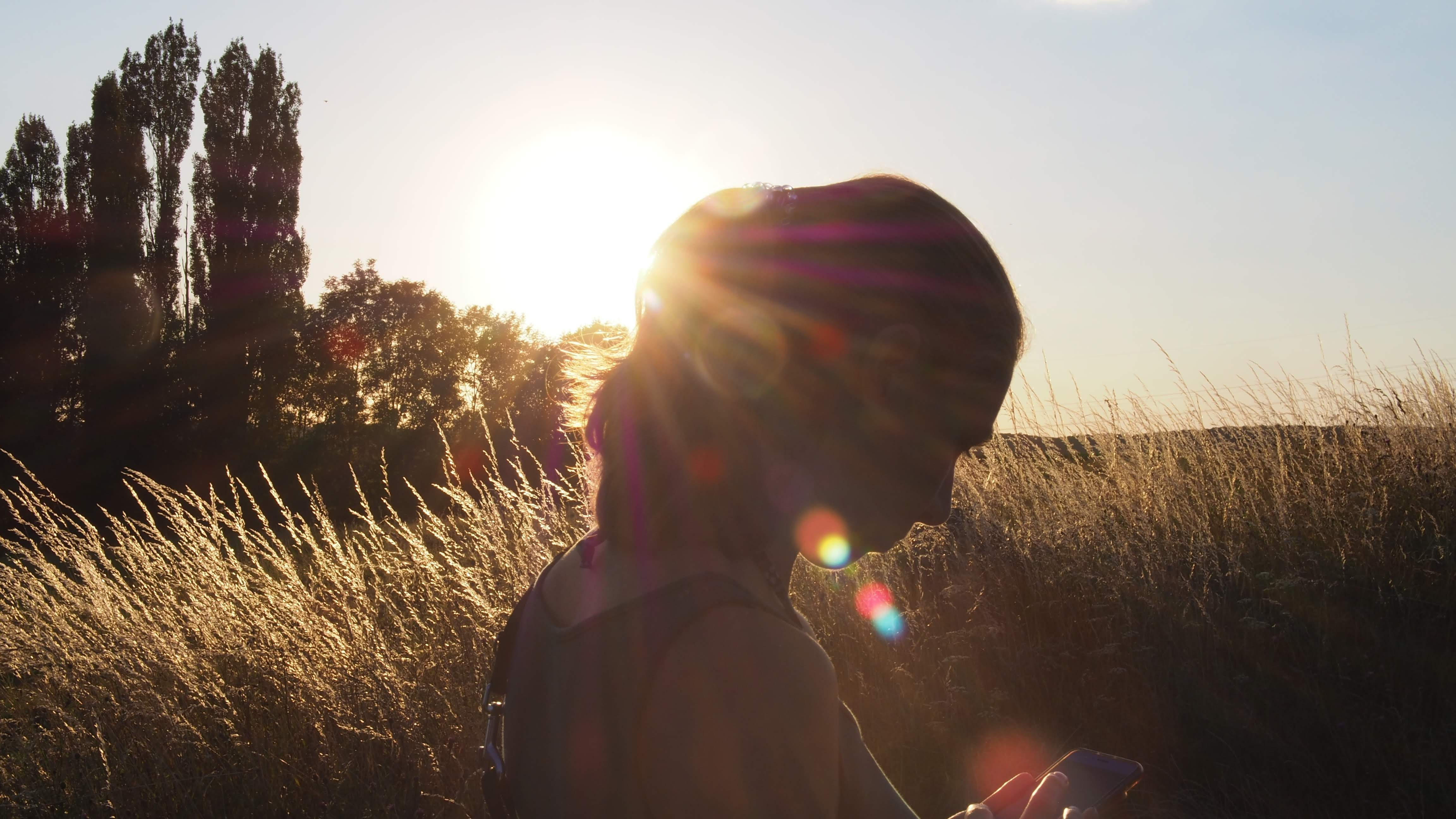 Silhouette of Woman Standing Near Green Grass Plants