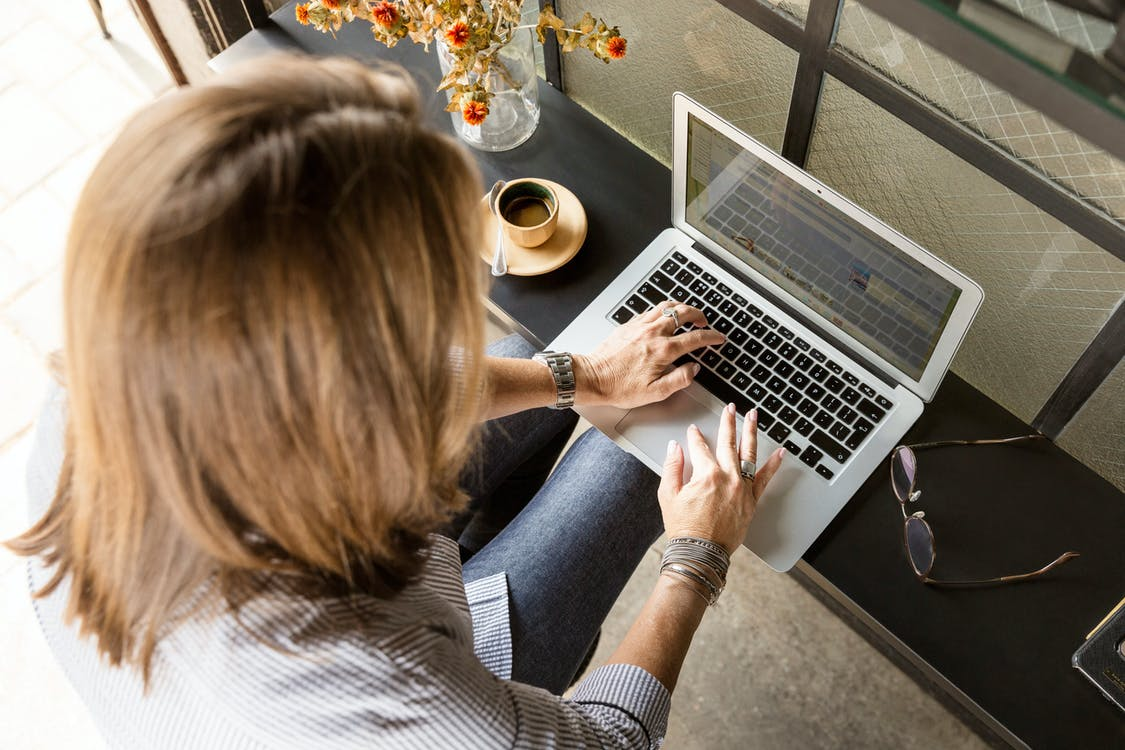 Person Sitting While Typing on Gray Laptop