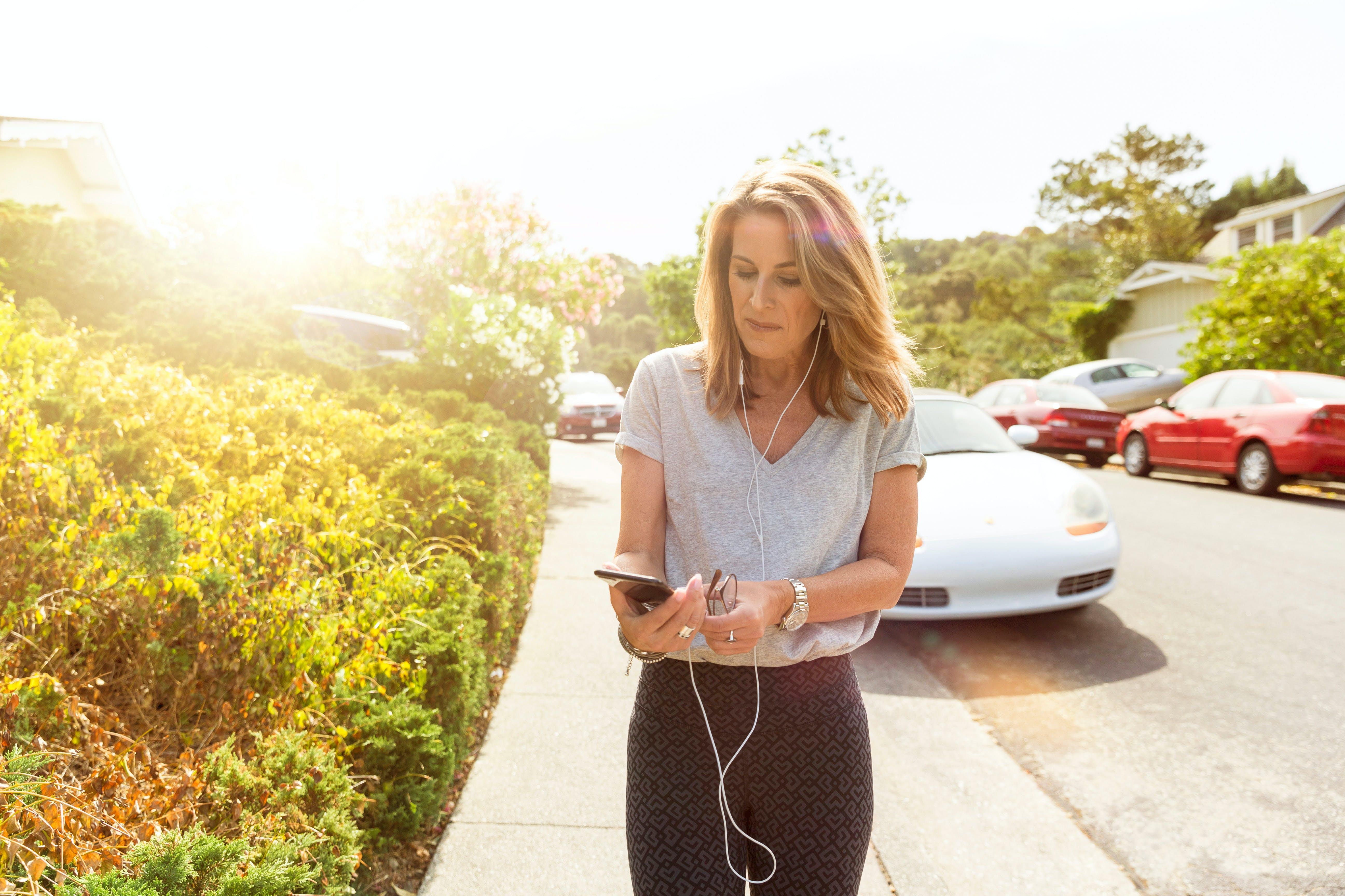 Women in Grey Shirt While Using Smartphone