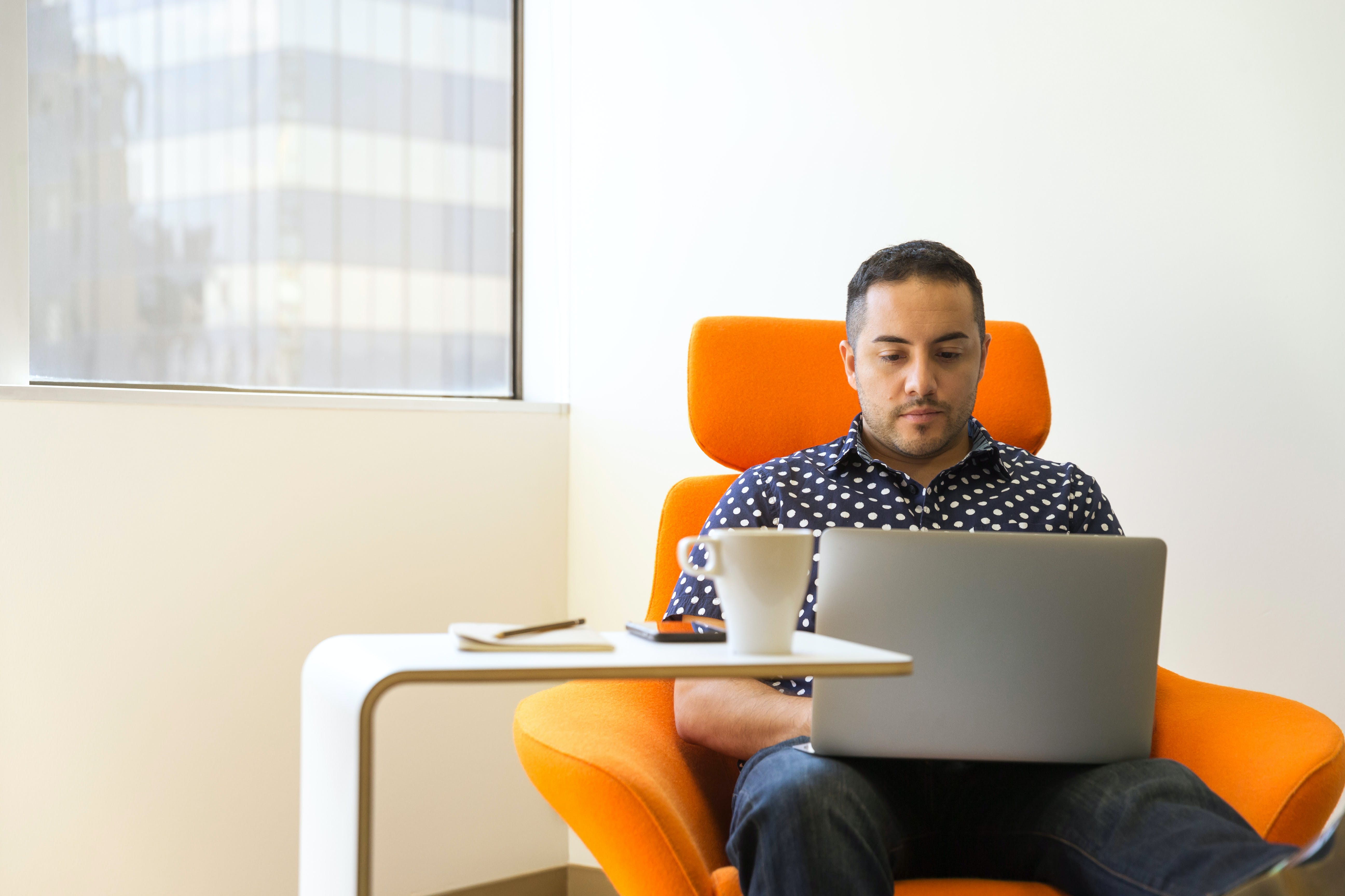 Man Sitting on Orange Sofa Chair With Gray Laptop Computer on His Lap