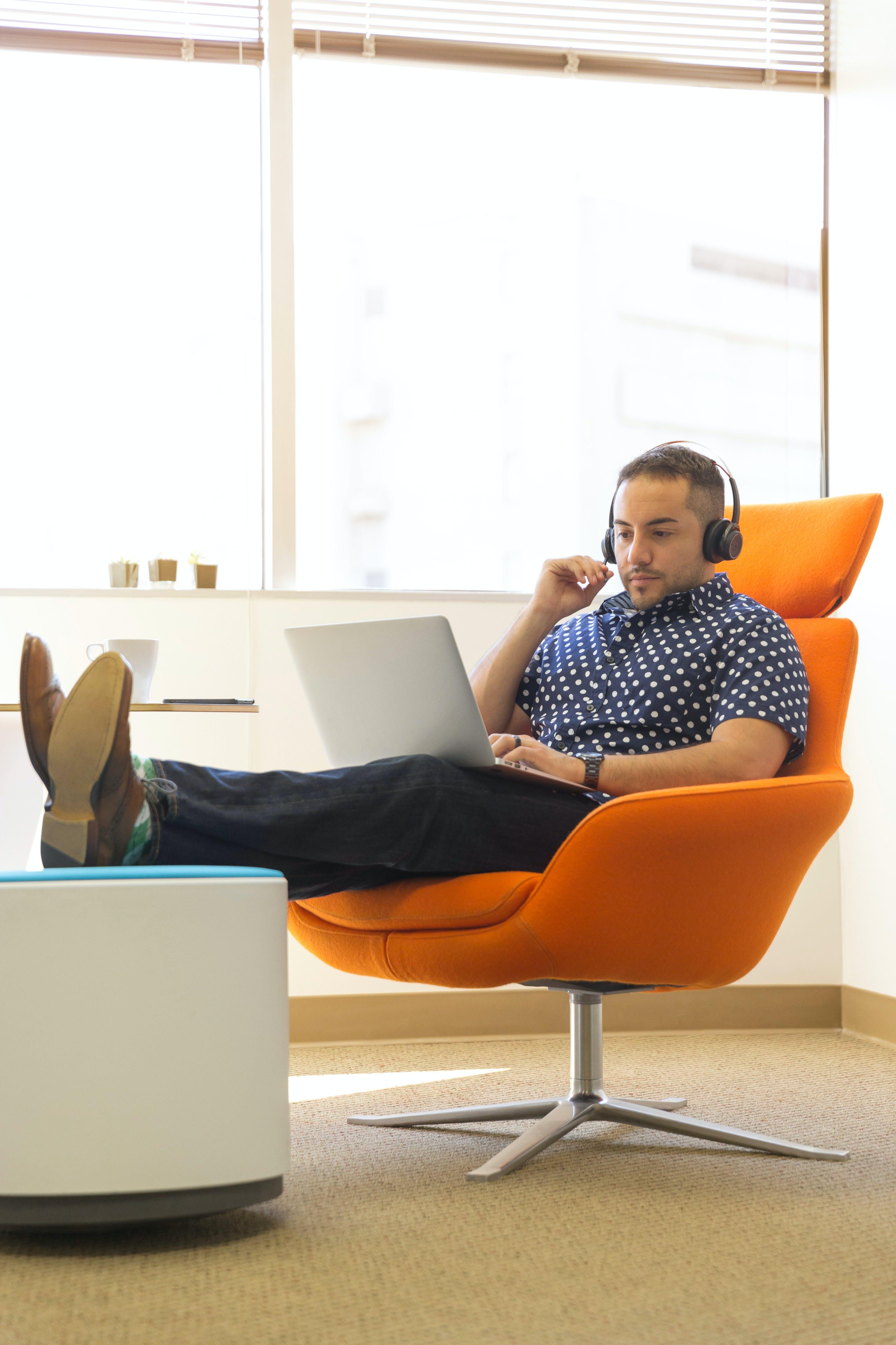 Man Wearing Headphones Sitting on Orange Padded Chair While Using Laptop Computer