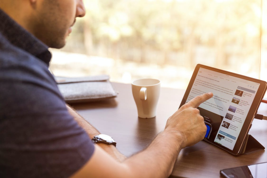 Man Using Ipad Sitting in Front of Desk