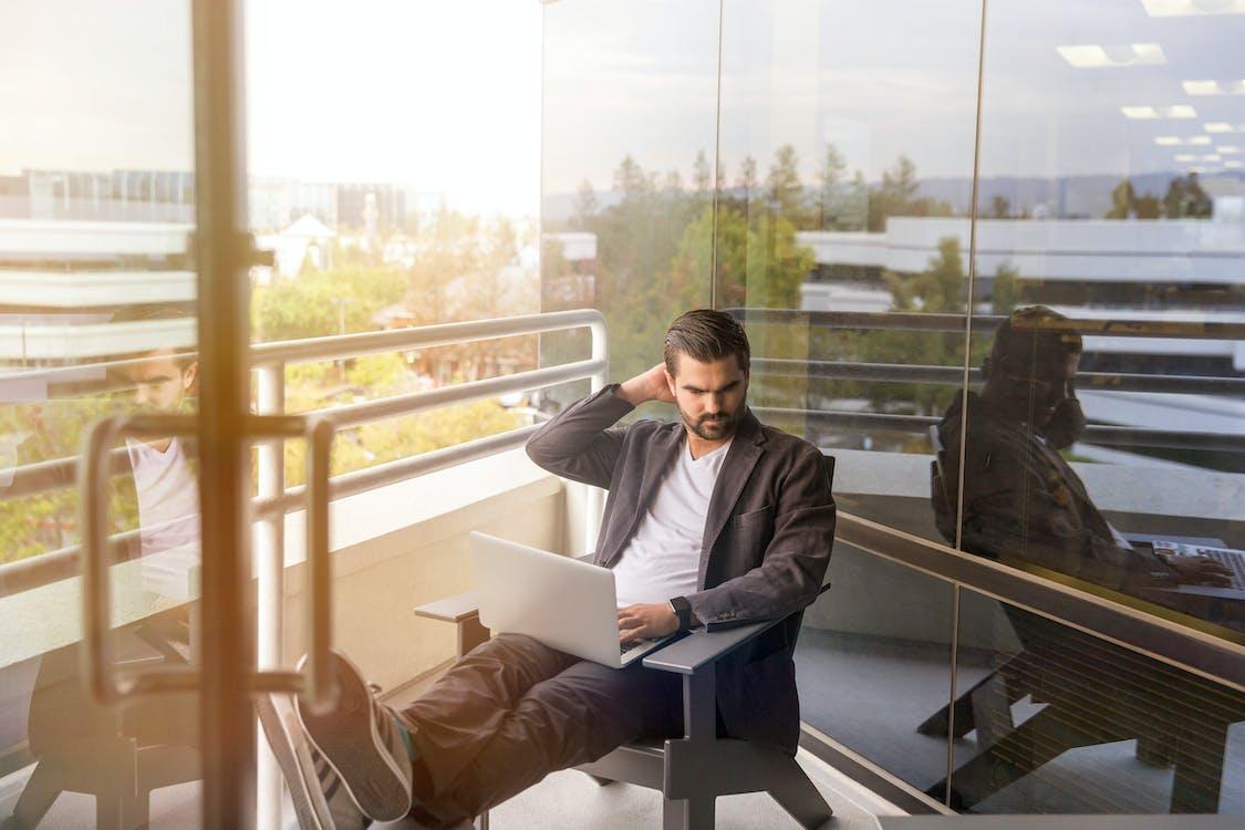 Mann Sitzt Während Der Verwendung Von Laptop
