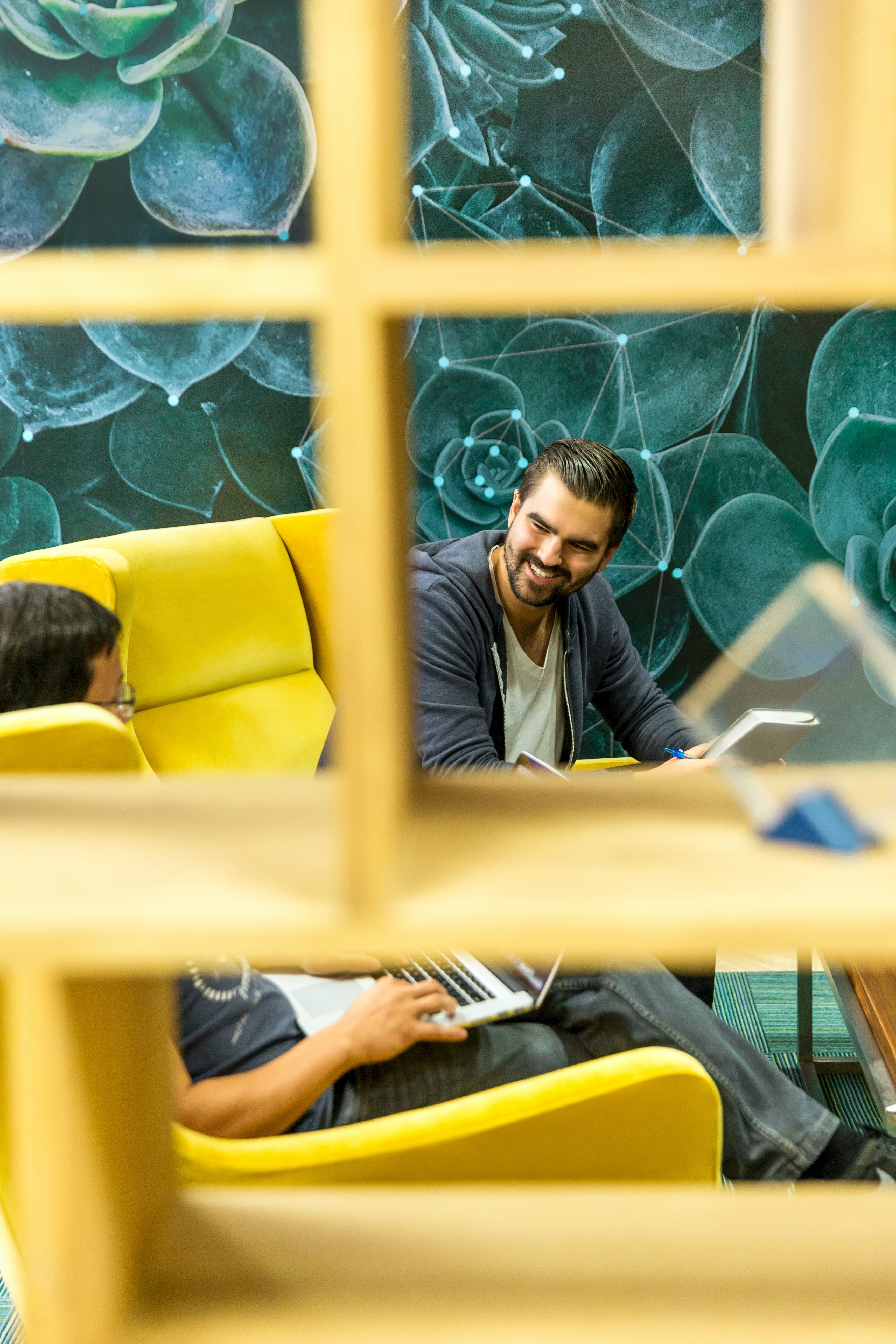 Window With the View of Man Holding Book While Sitting Beside Man Using Laptop