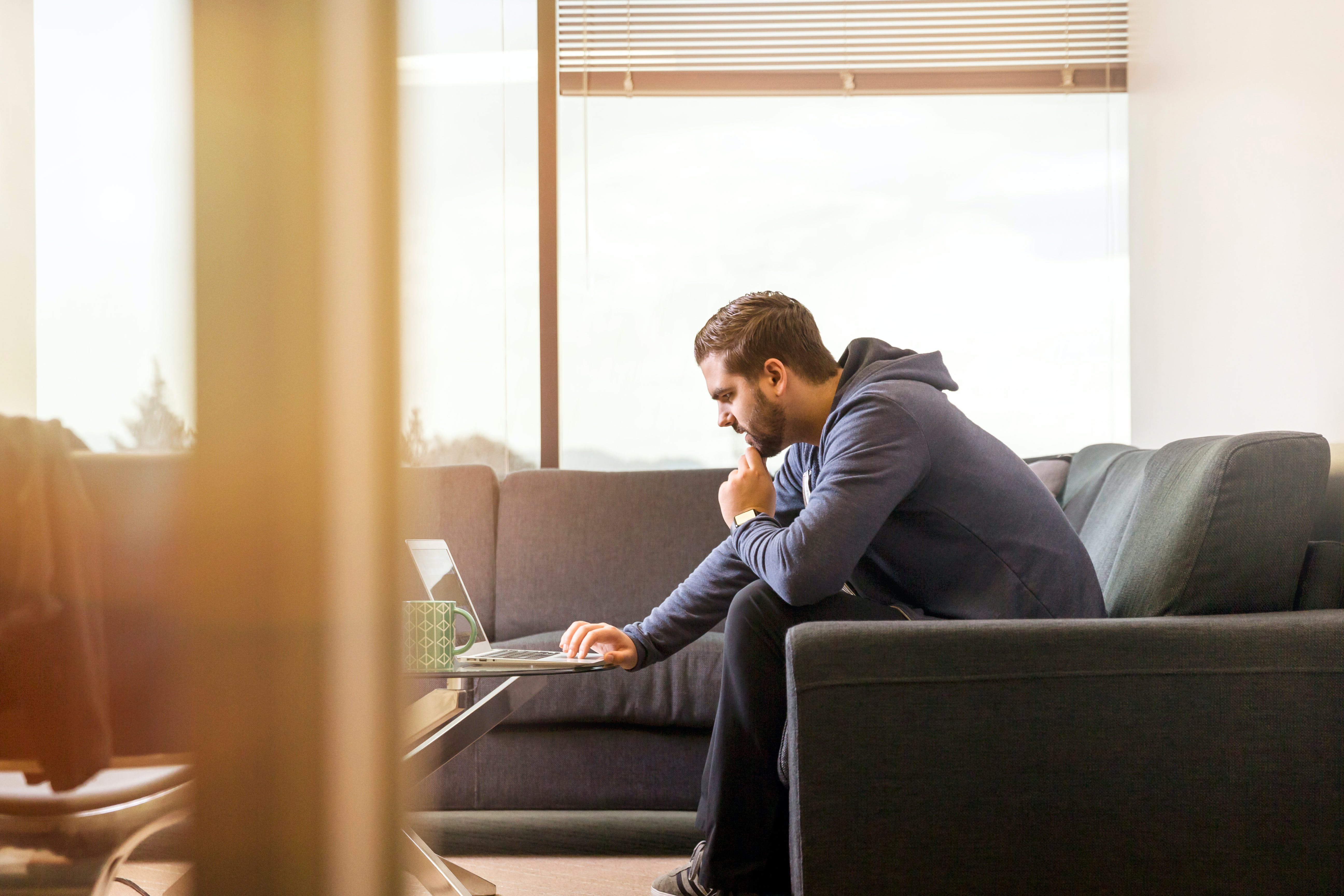 Man Using Laptop Sitting on Couch