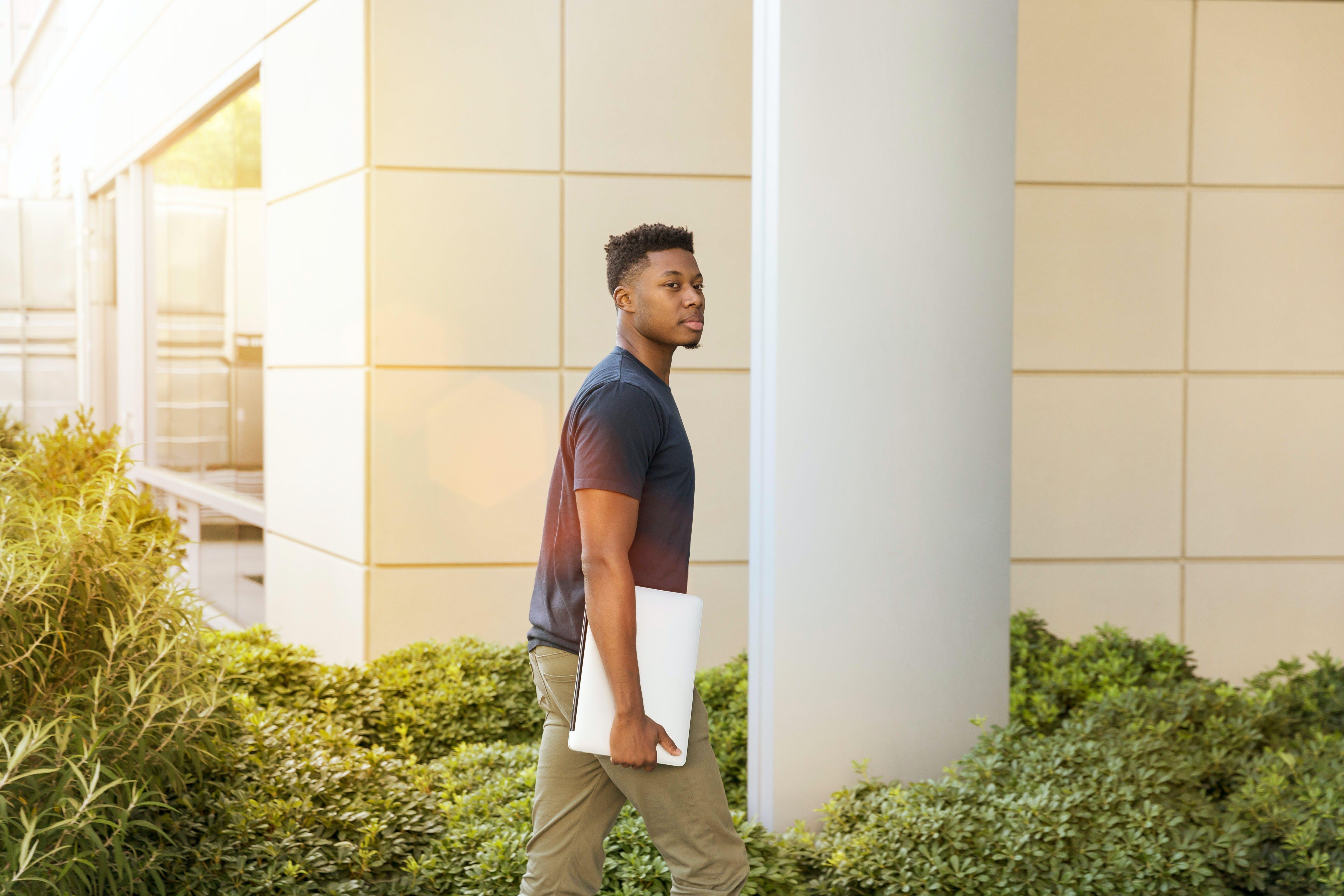 Man Walking Beside Green Leafed Plants Near White Concrete Pillar