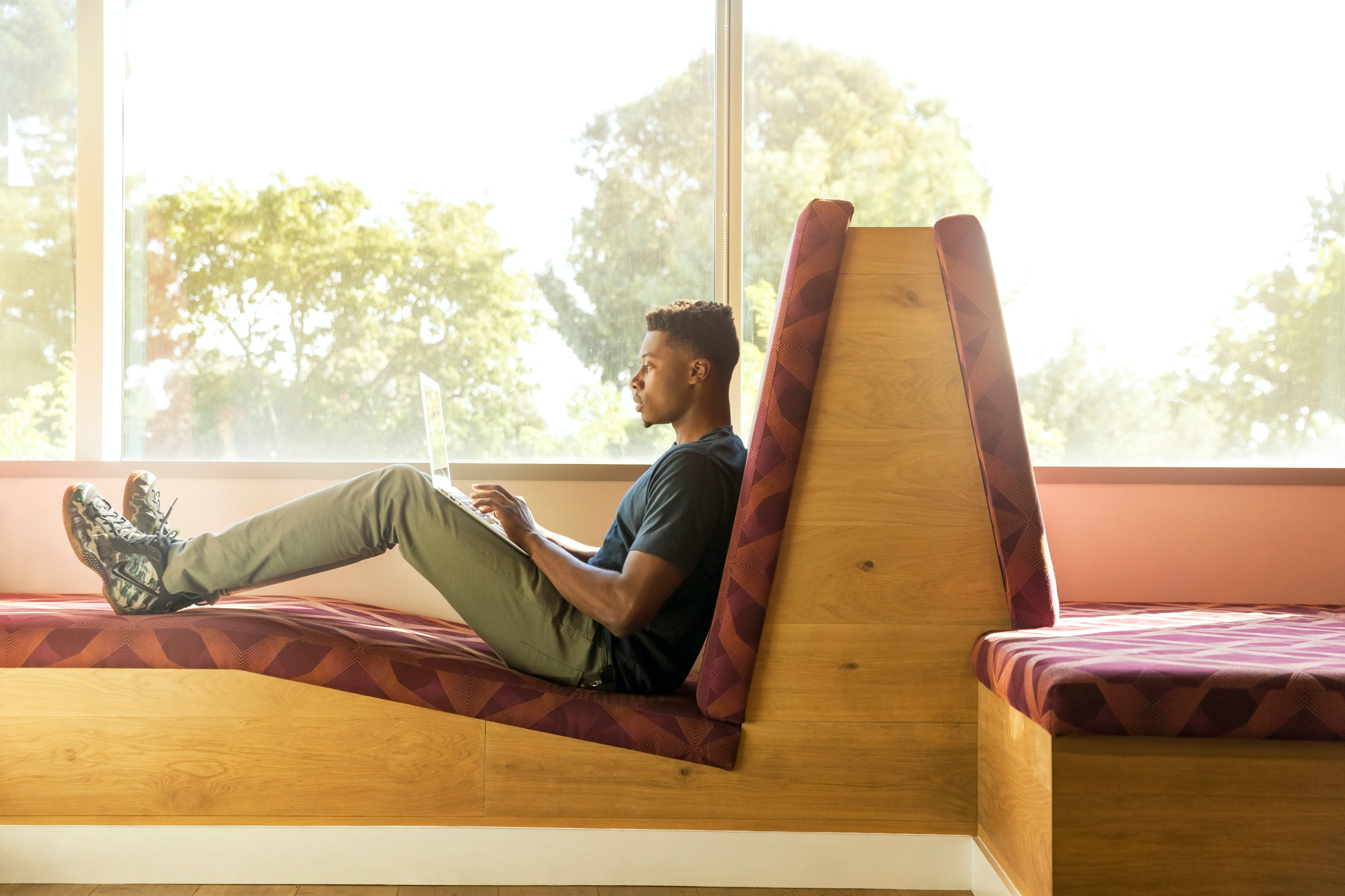 Man Sitting on Maroon and Brown Fabric Padded Sofa Using Laptop Beside Glass Window