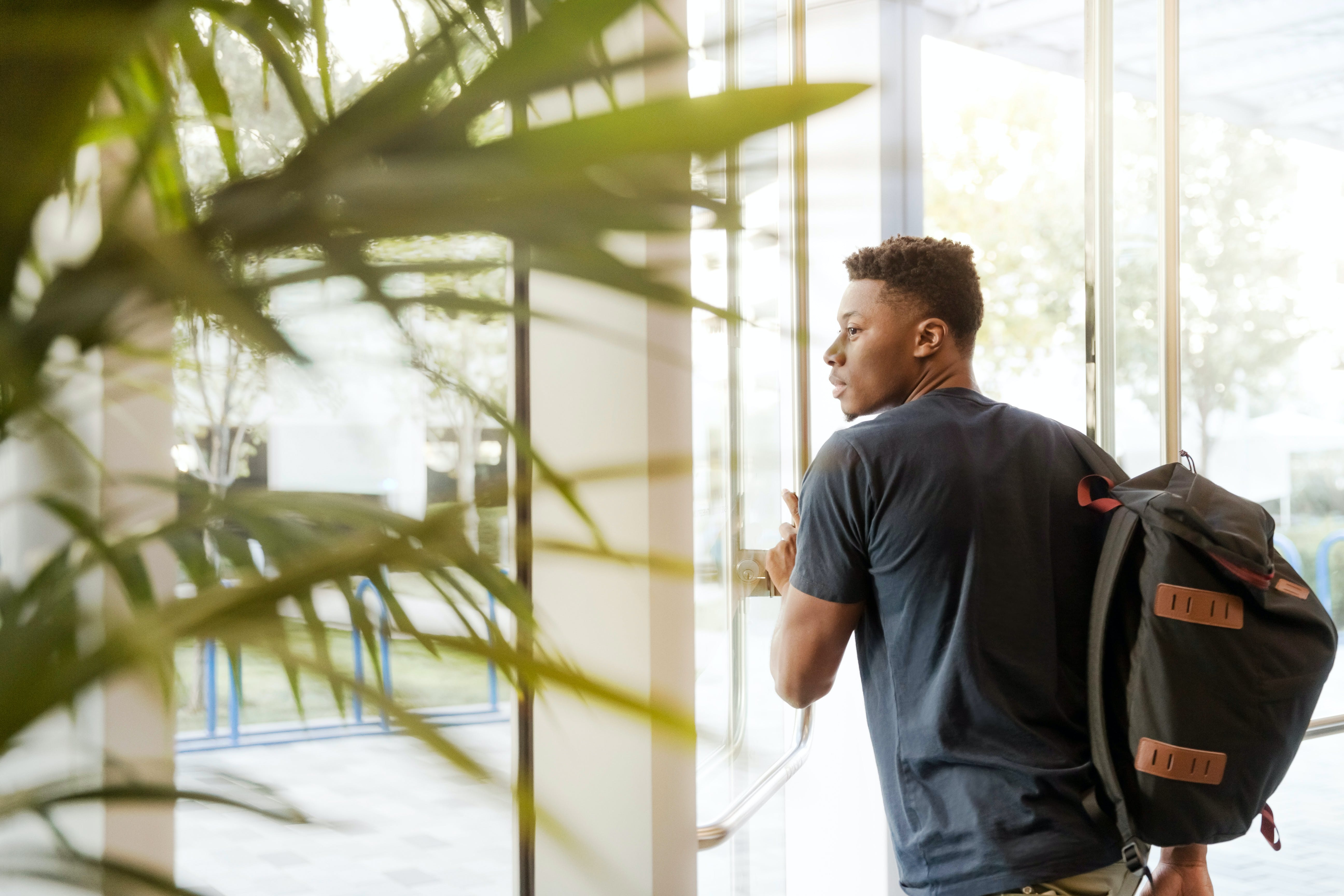 Man Looking Outside Window Carrying Black and Brown Backpack While Holding His Hand on Window