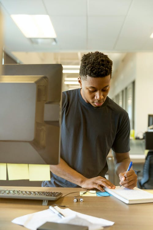 Uomo Che Scrive Sul Taccuino Bianco Sull'ufficio