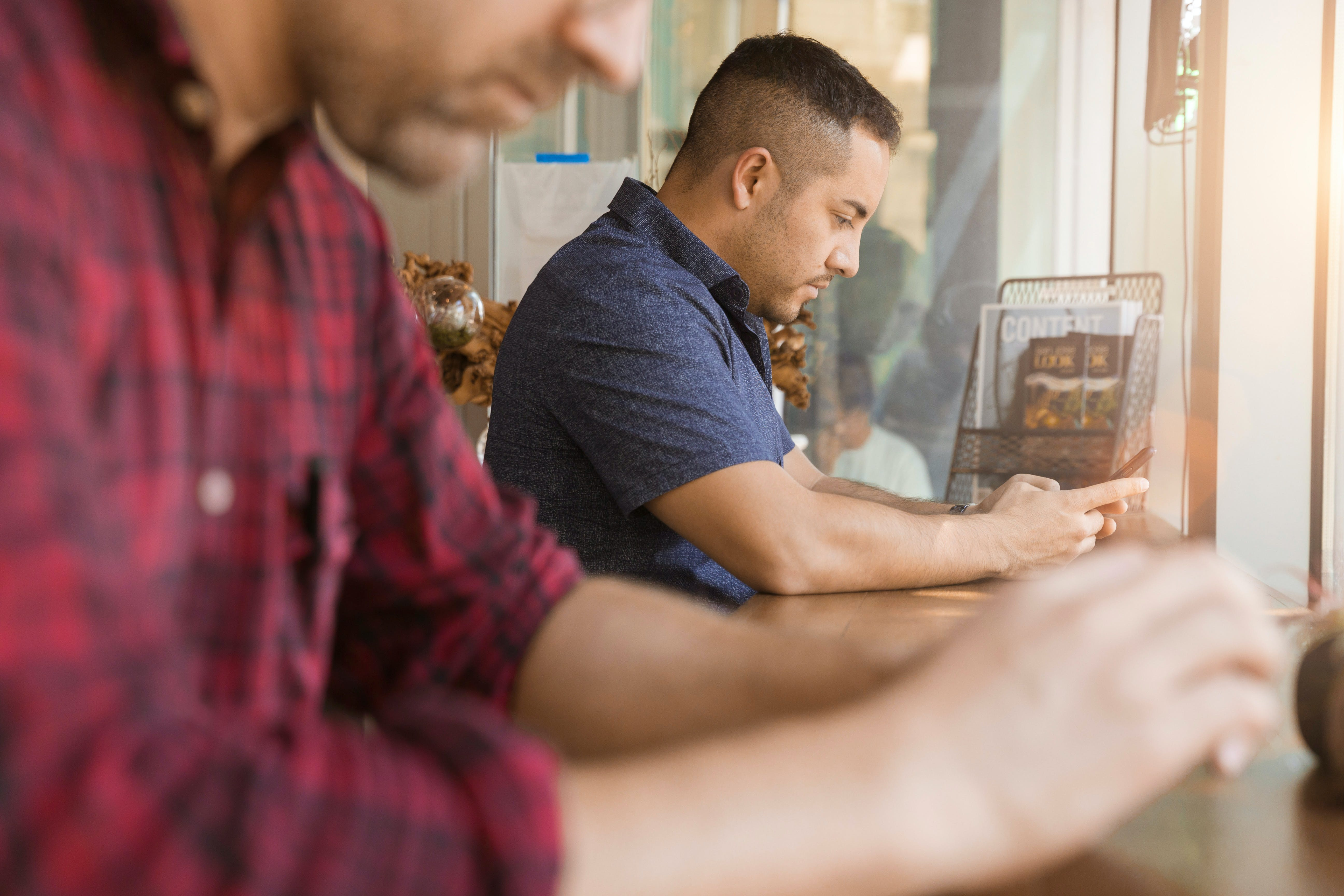 Man Using Smartphone Sitting Beside Table and Man
