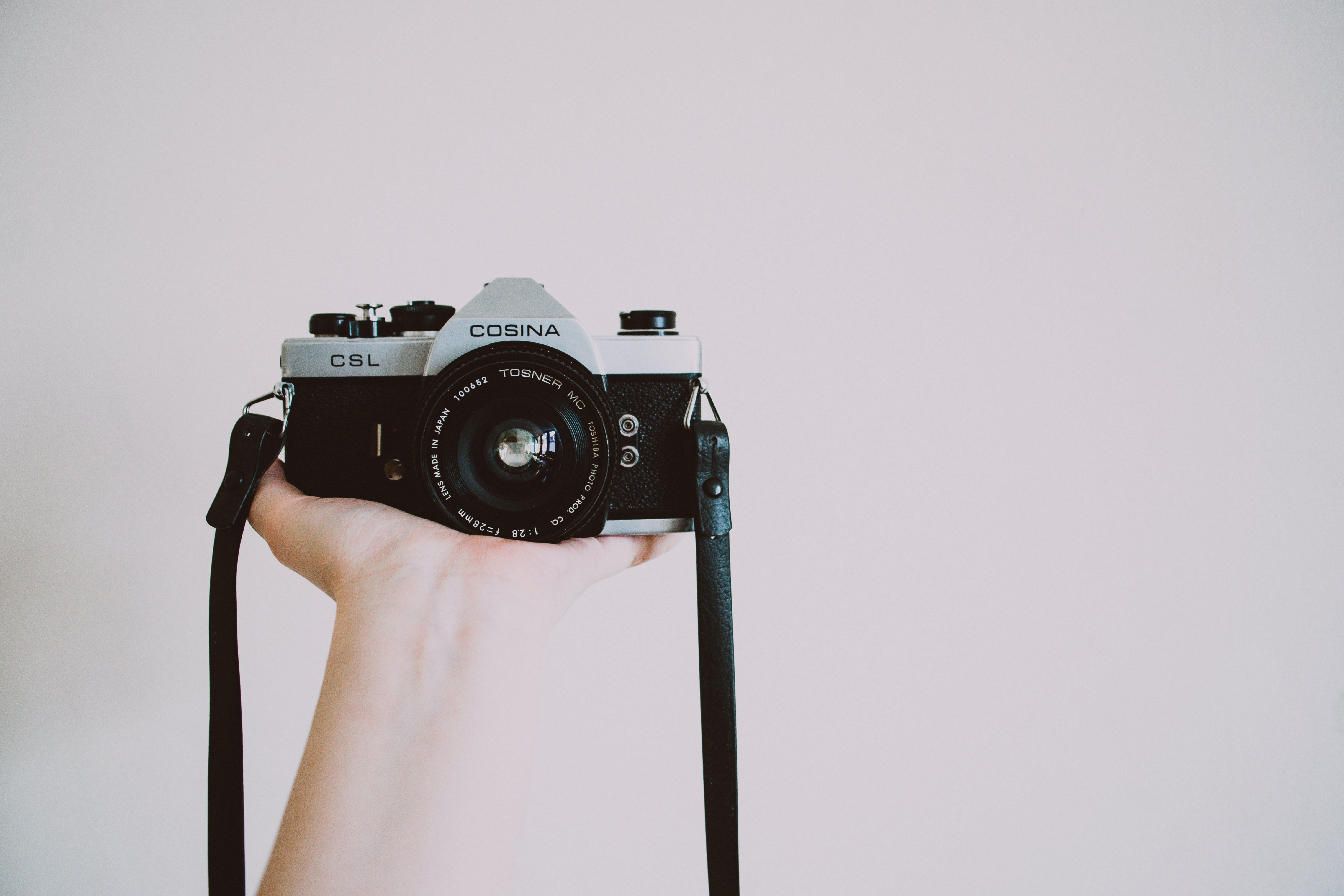 Photography of Person Holding Cosina Camera