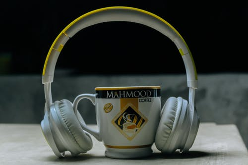 Close-Up Photography of Headset Near Cup
