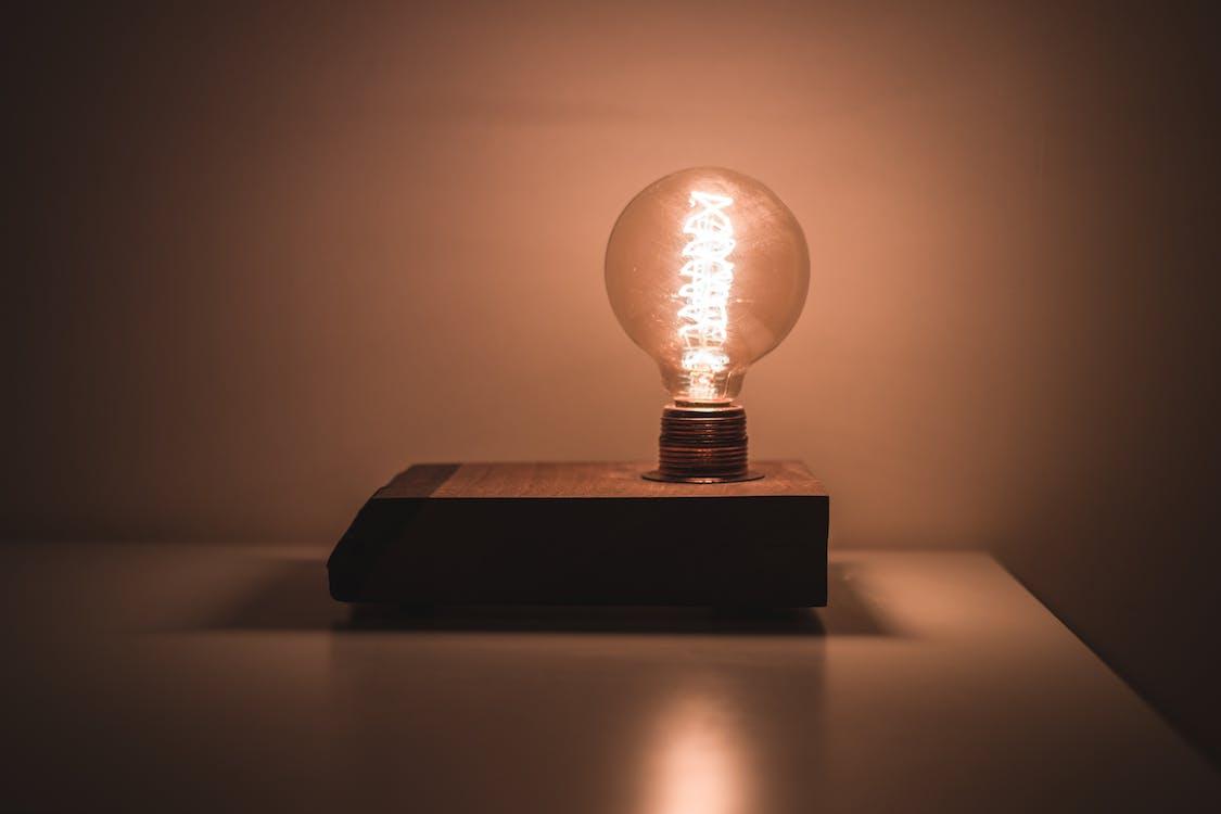 Light Bulb on White Desk Turned on