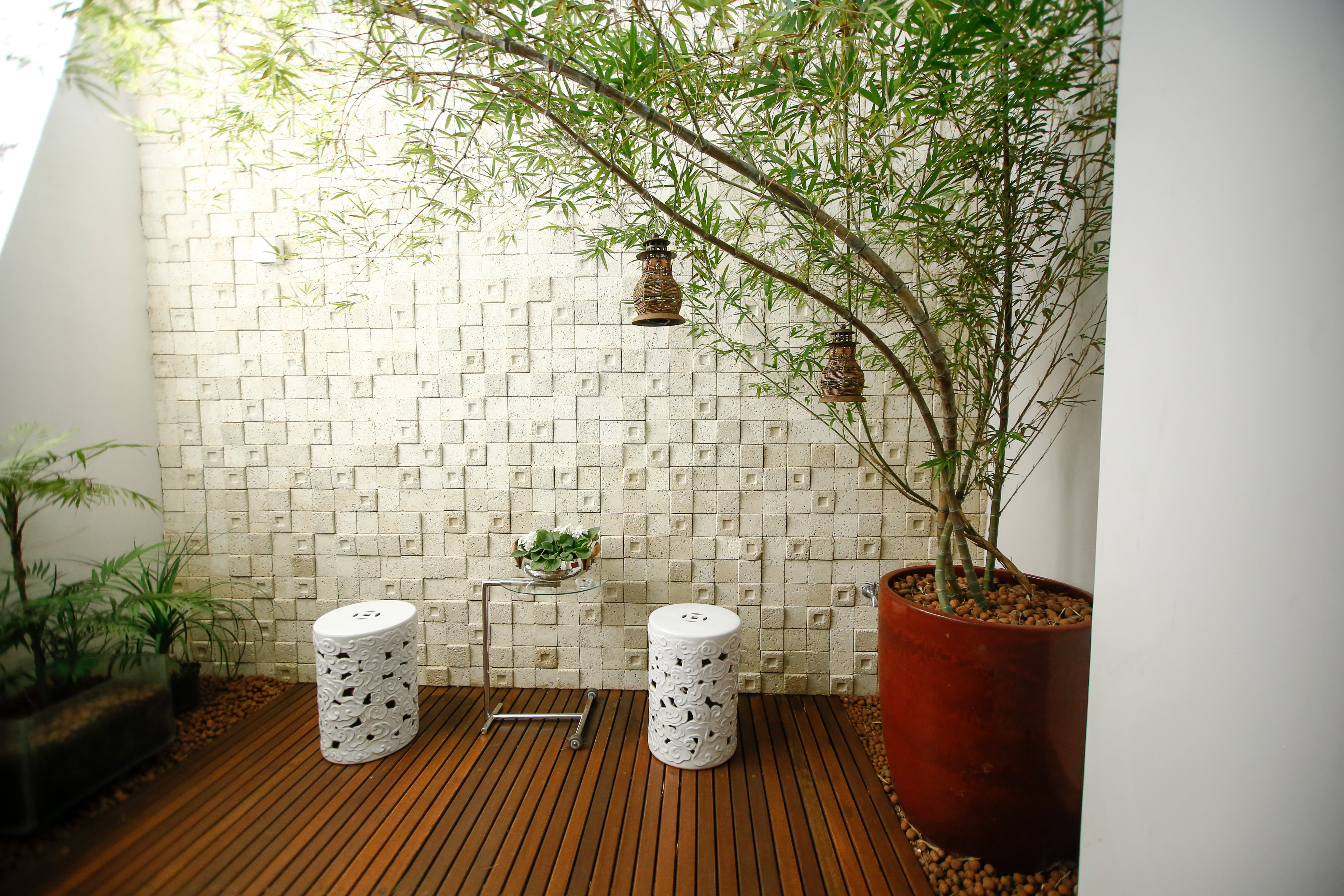 Two White Concrete Columns Beside Concrete Wall and Green Plants