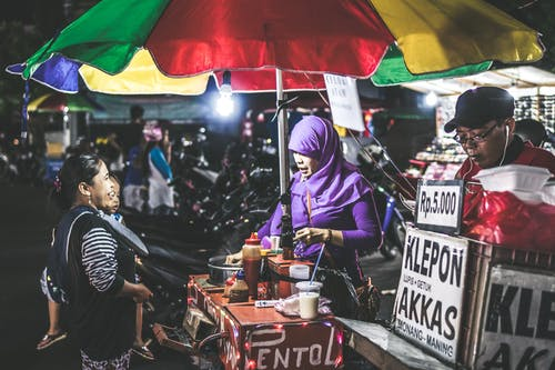 Woman Wearing Purple Hijab Selling Food