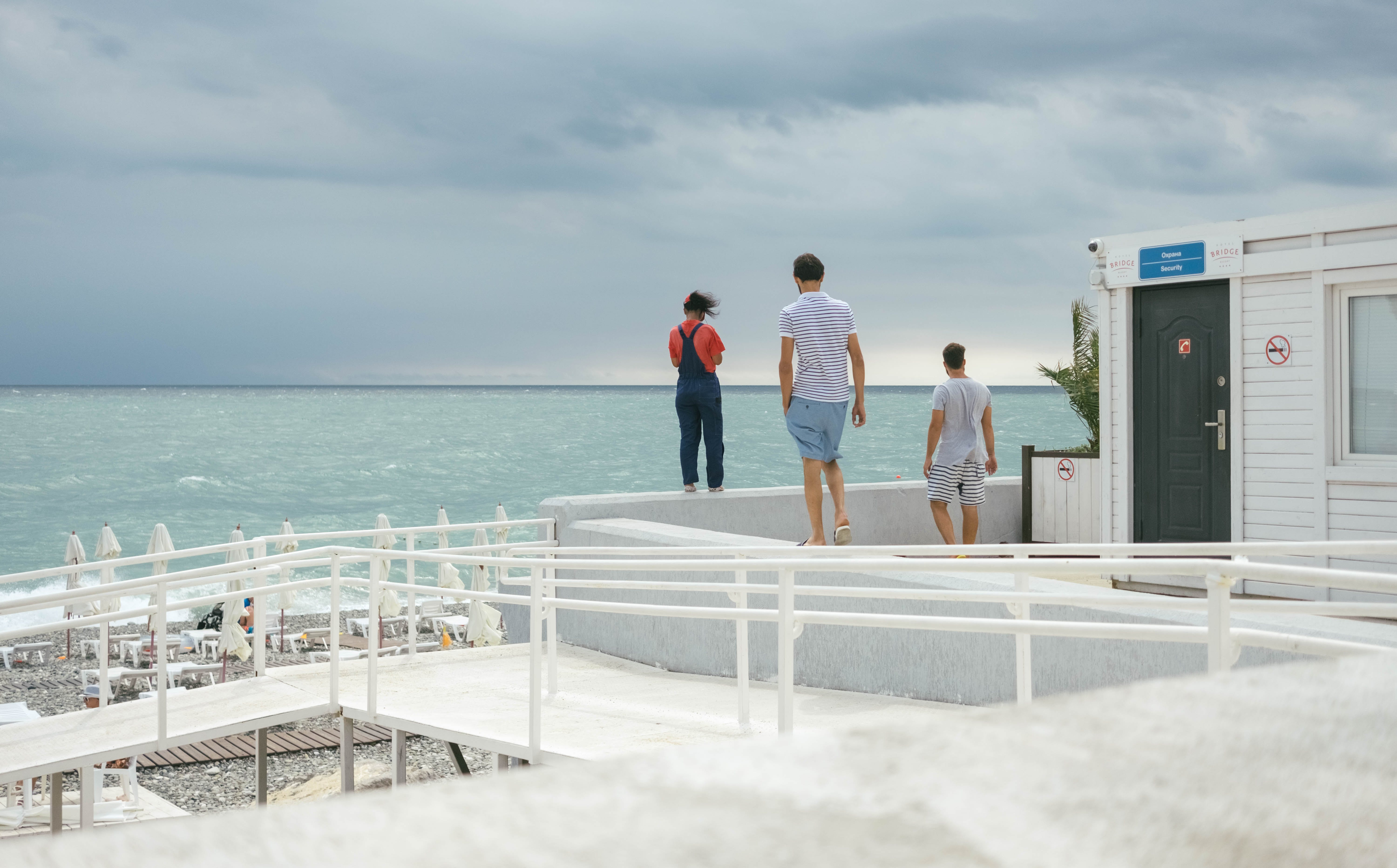Three People Standing on White Surface Near Body of Water