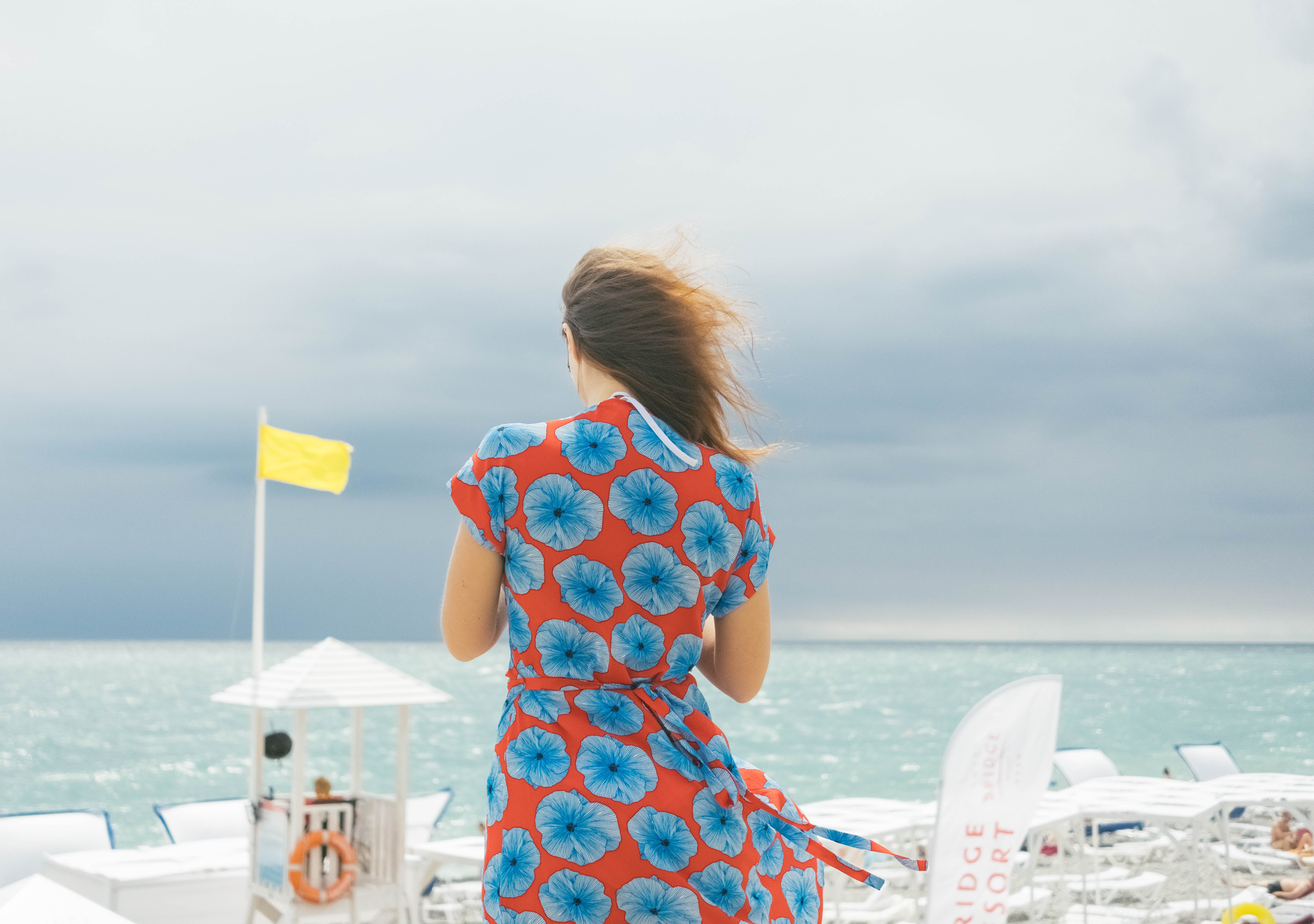 Woman in Red and Blue Floral Dress Standing Near Body of Water