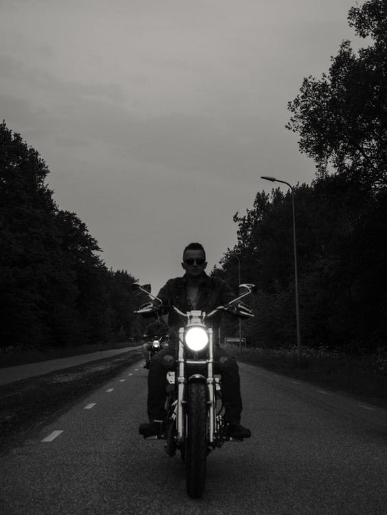 Grayscale Photo of Man Riding Motorcycle on the Road