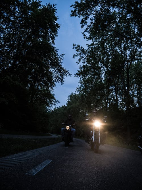 Two Men Riding Motorcycle on Road during Nighttime
