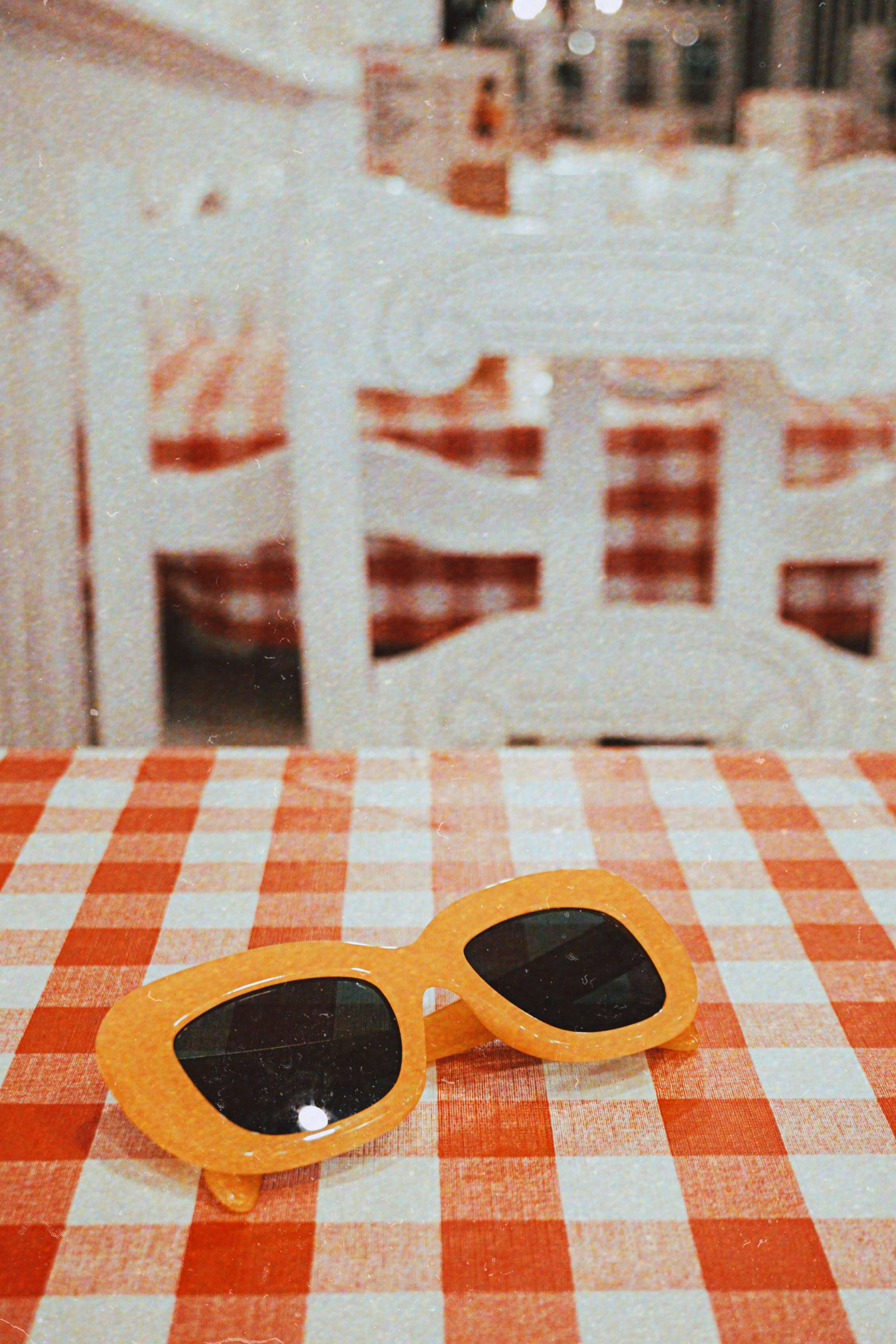 Sunglasses With Orange Frames on Checkered Tablecloth
