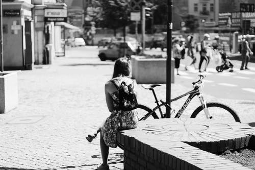 Grayscale Photo of Woman Sitting Near Bicycle