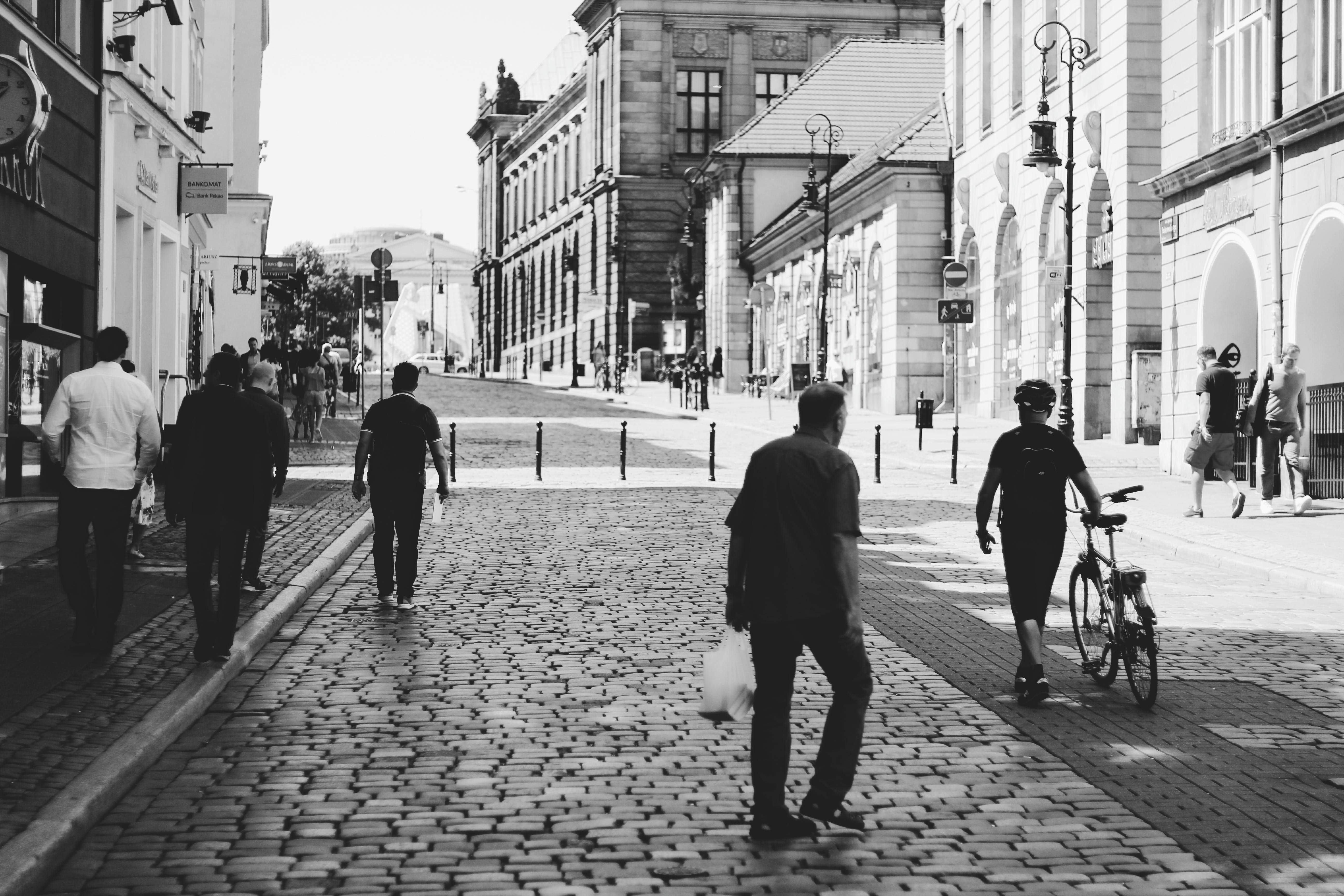 Men Walking on Road With Buildings on the Side