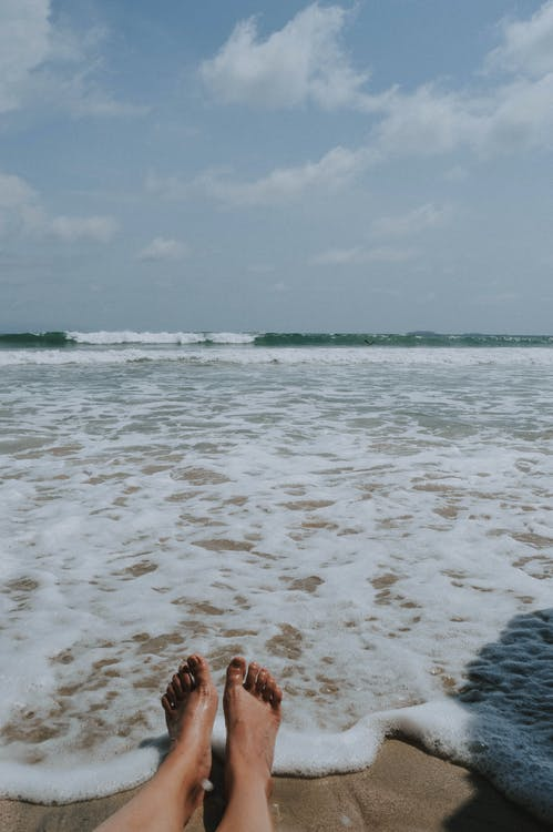 Person Sitting on Brown Seashore
