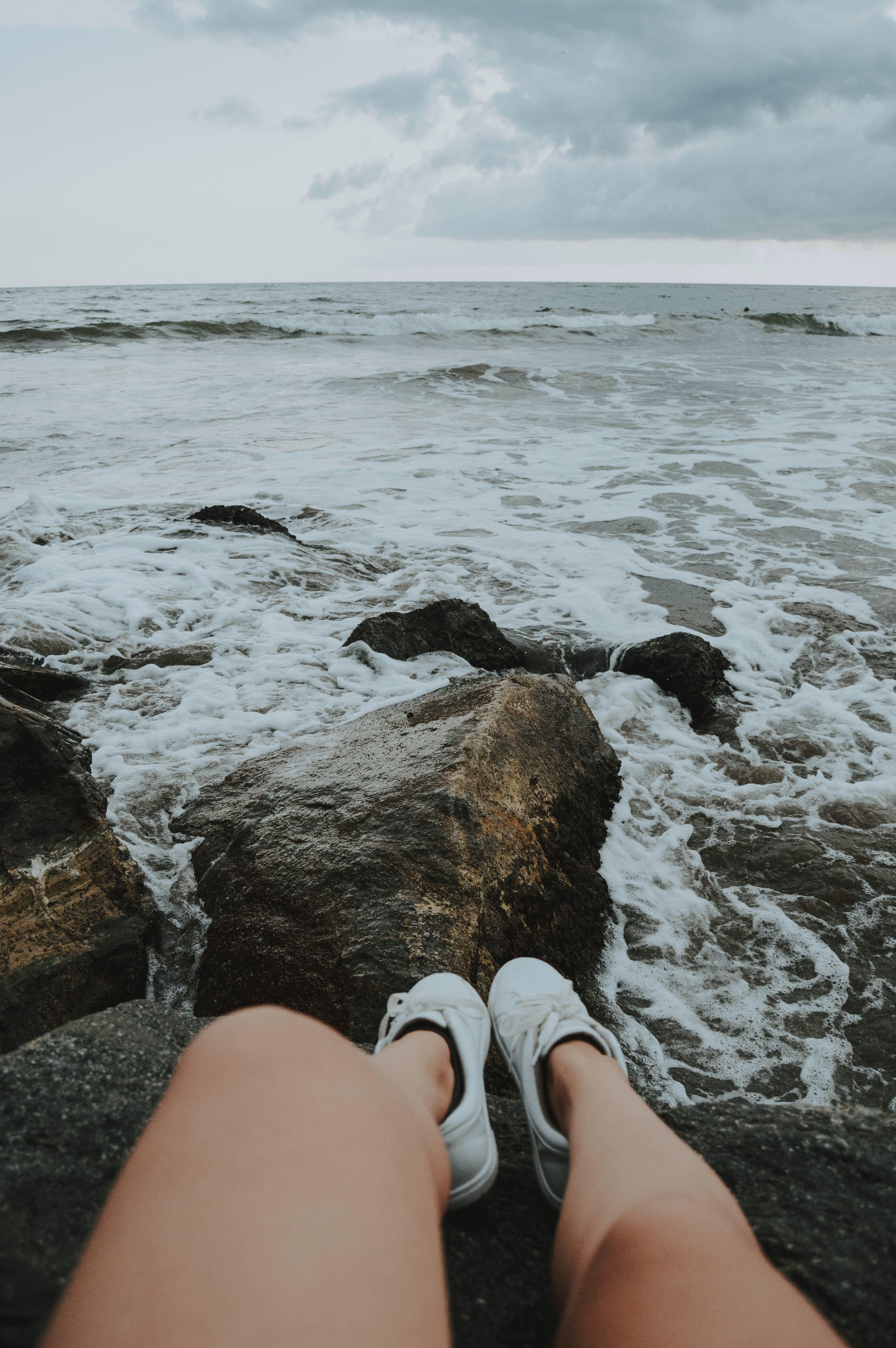 Person Sitting on Rocks
