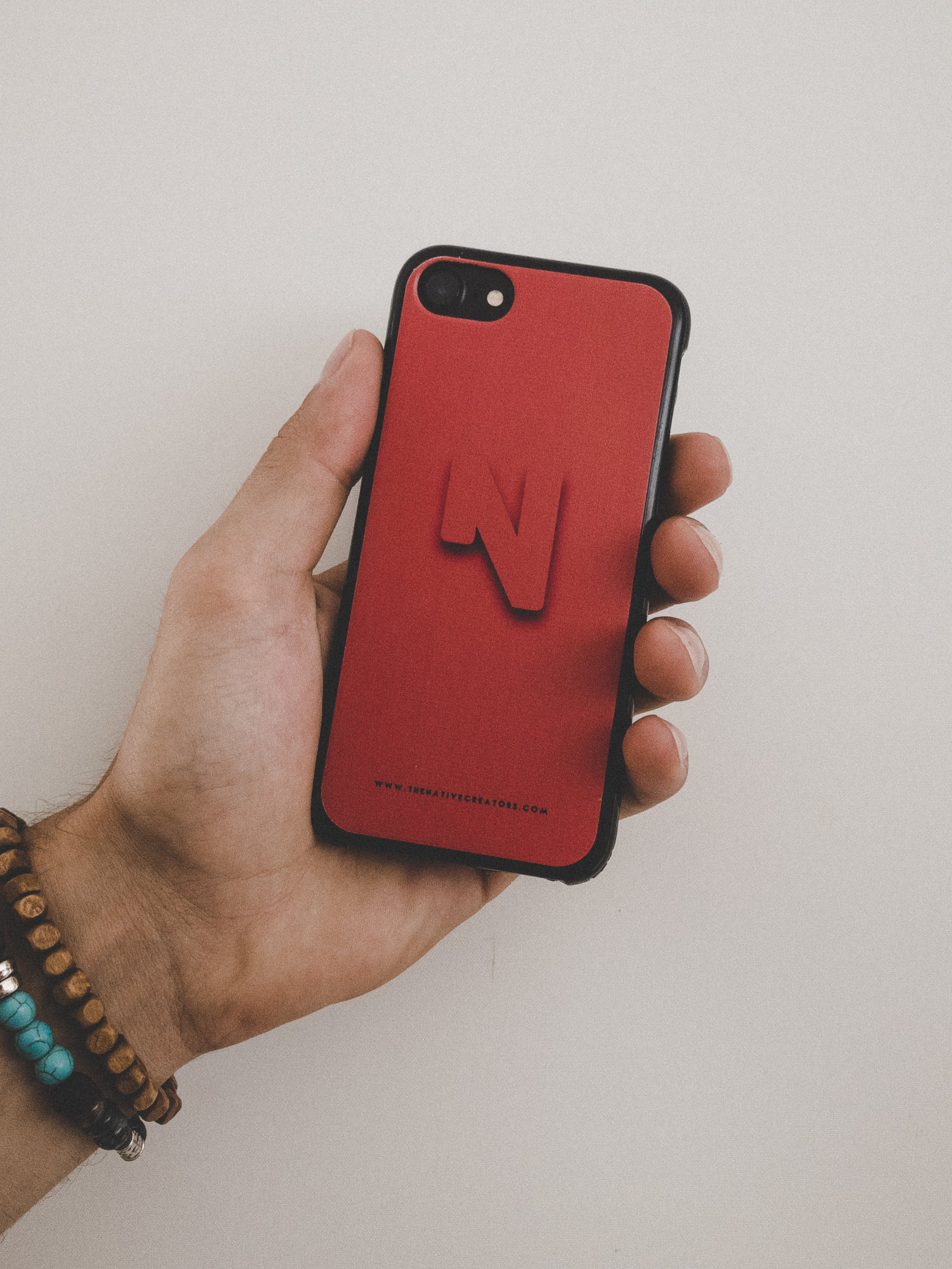 Person Holding Black Iphone 7 and Red Case Screenshot