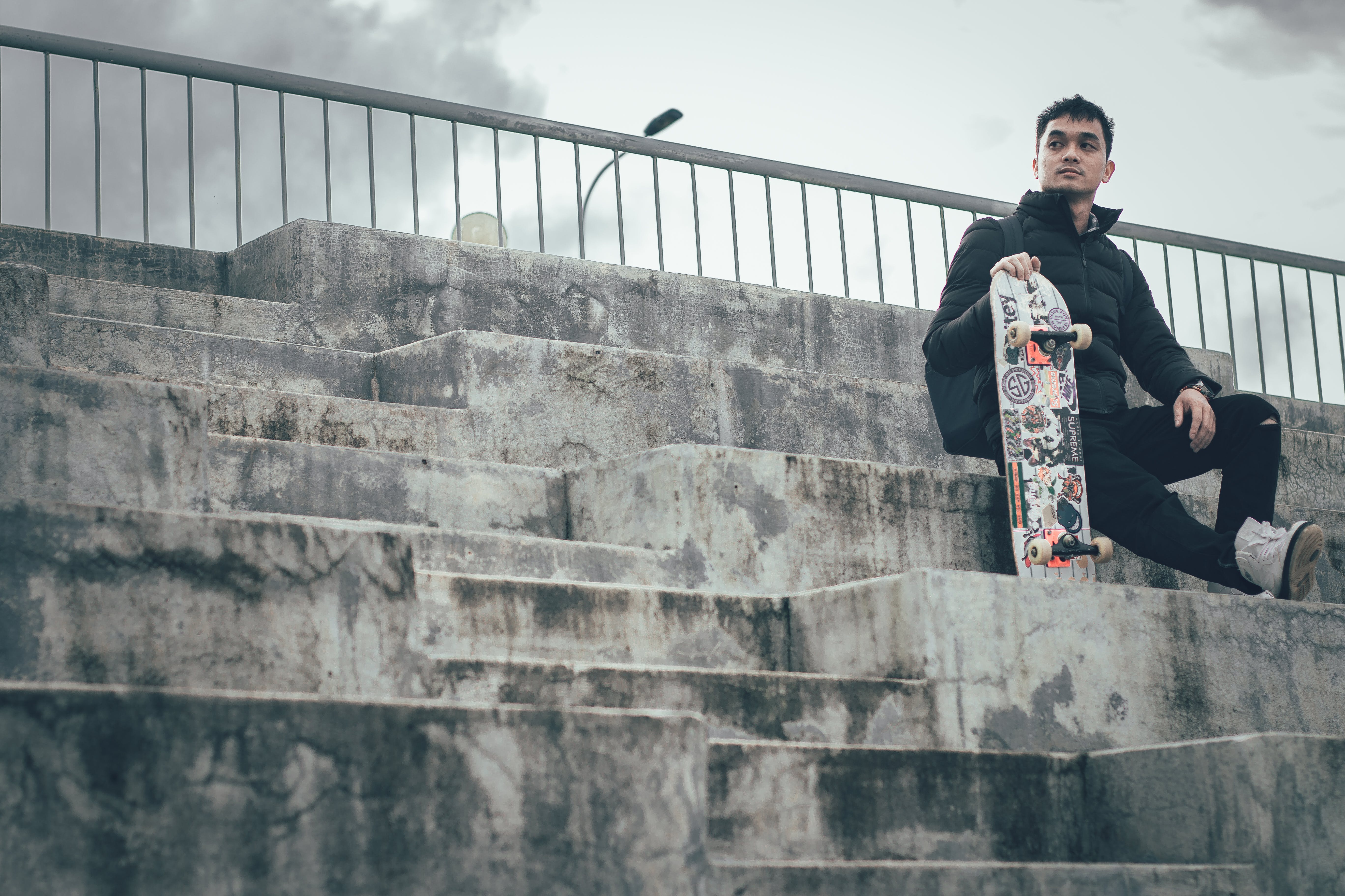Man Holding Skateboard Sitting On Stairs
