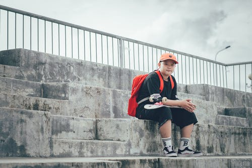Boy Wearing Black Shirt Sitting On Concrete Staircase Holding Skateboard