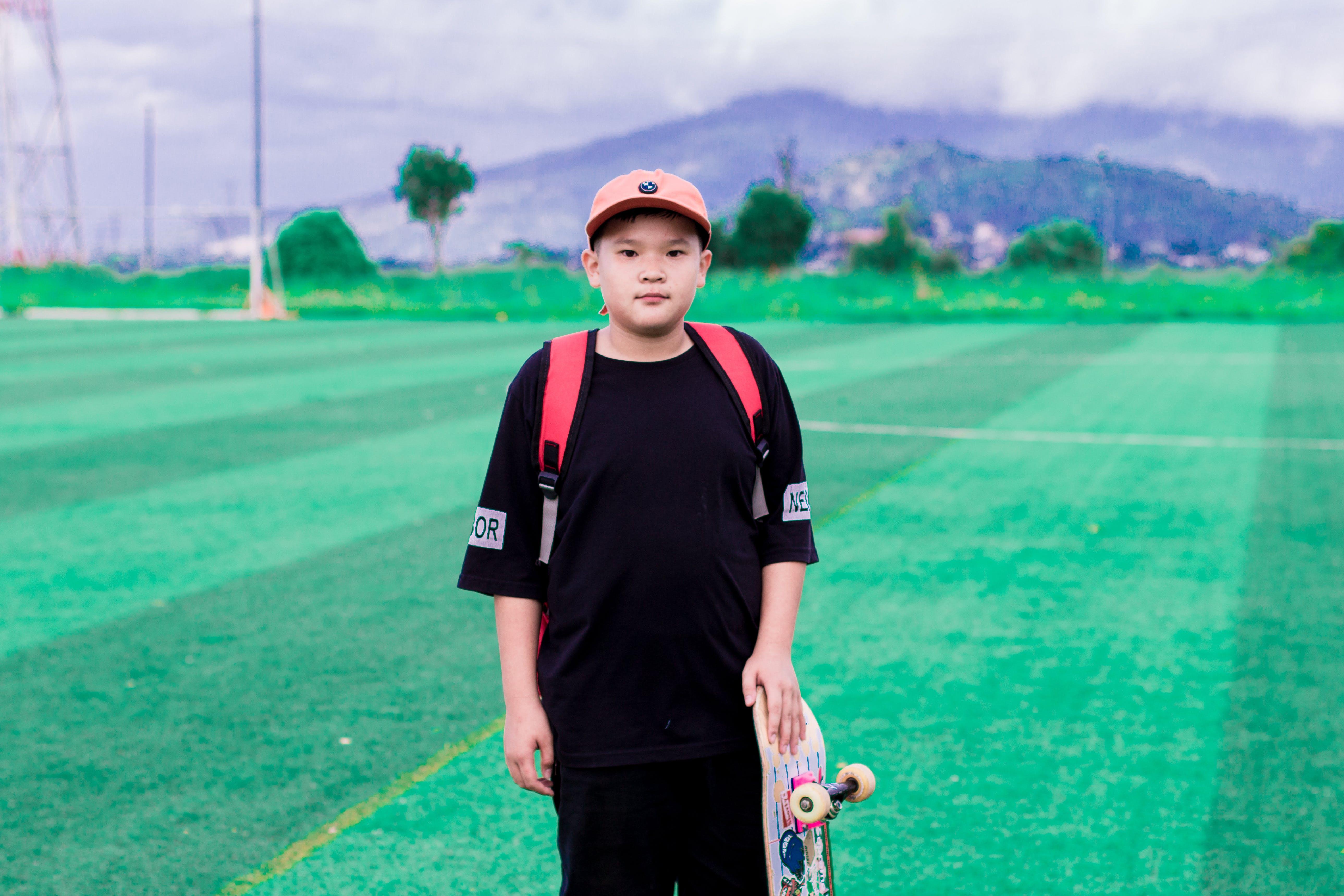 Photo of Boy Holding Skateboard