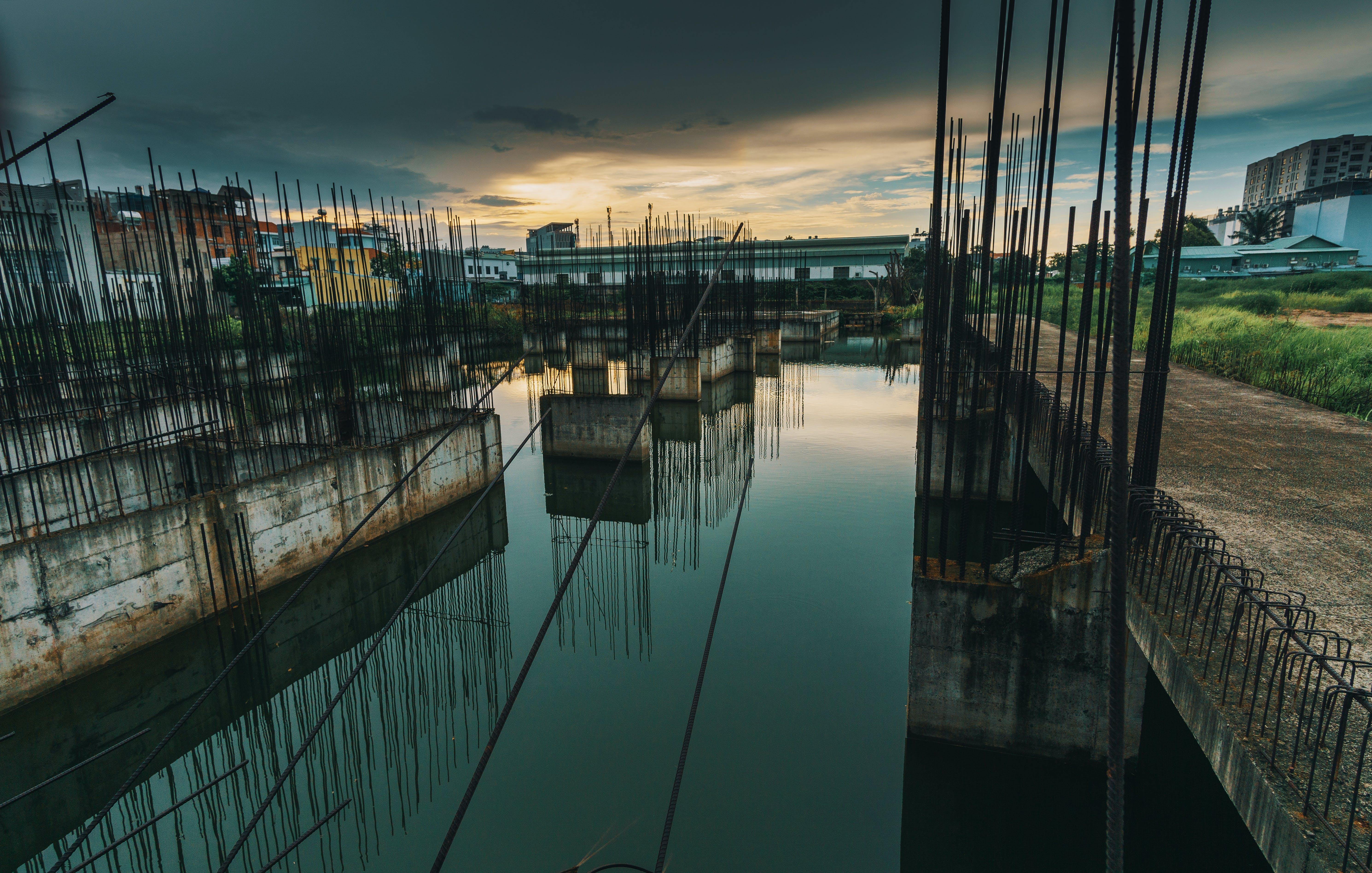 Photo of Metal Bars on Water Under Dark Sky