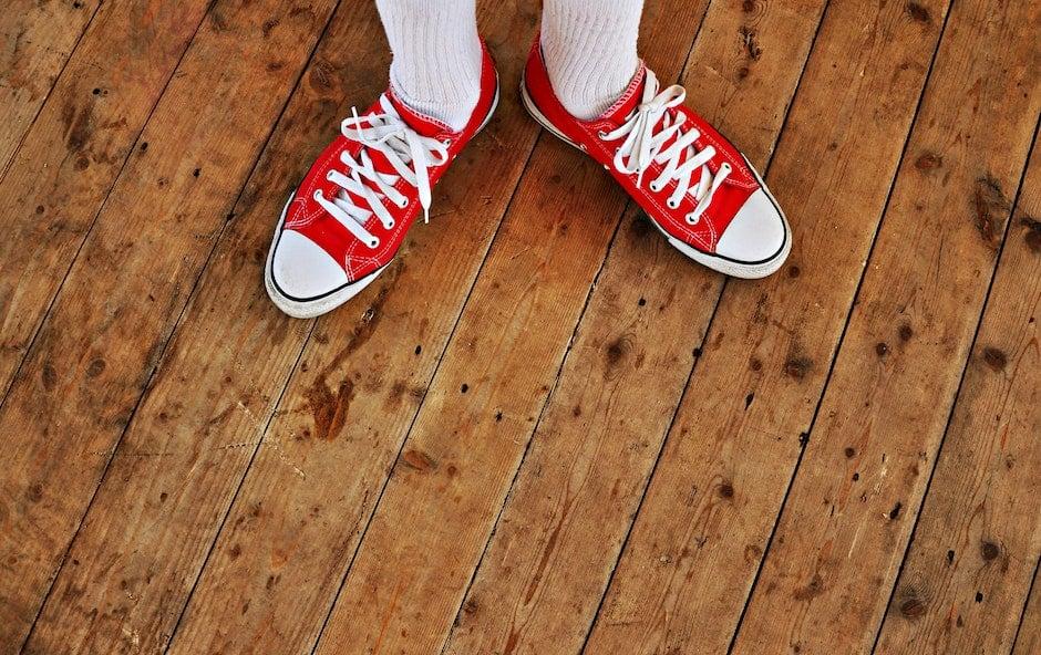 Person in Red Low Tops in Brown Wooden Floor