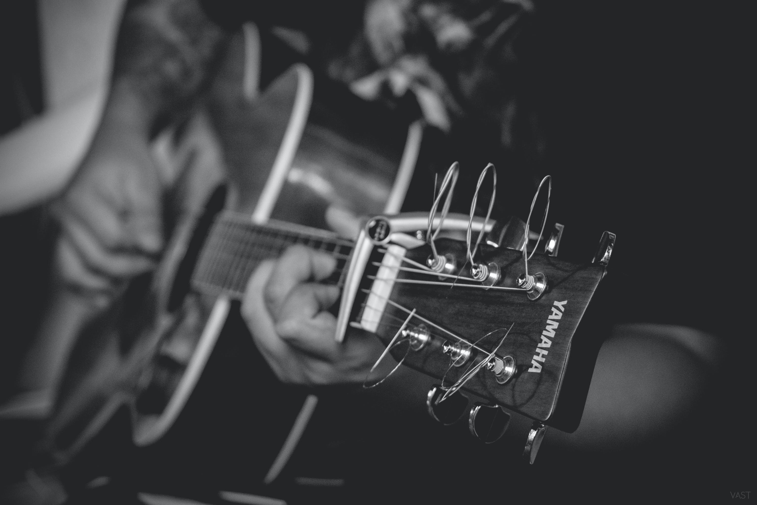 Grayscale Photography of Person Playing Yamaha Acoustic Guitar
